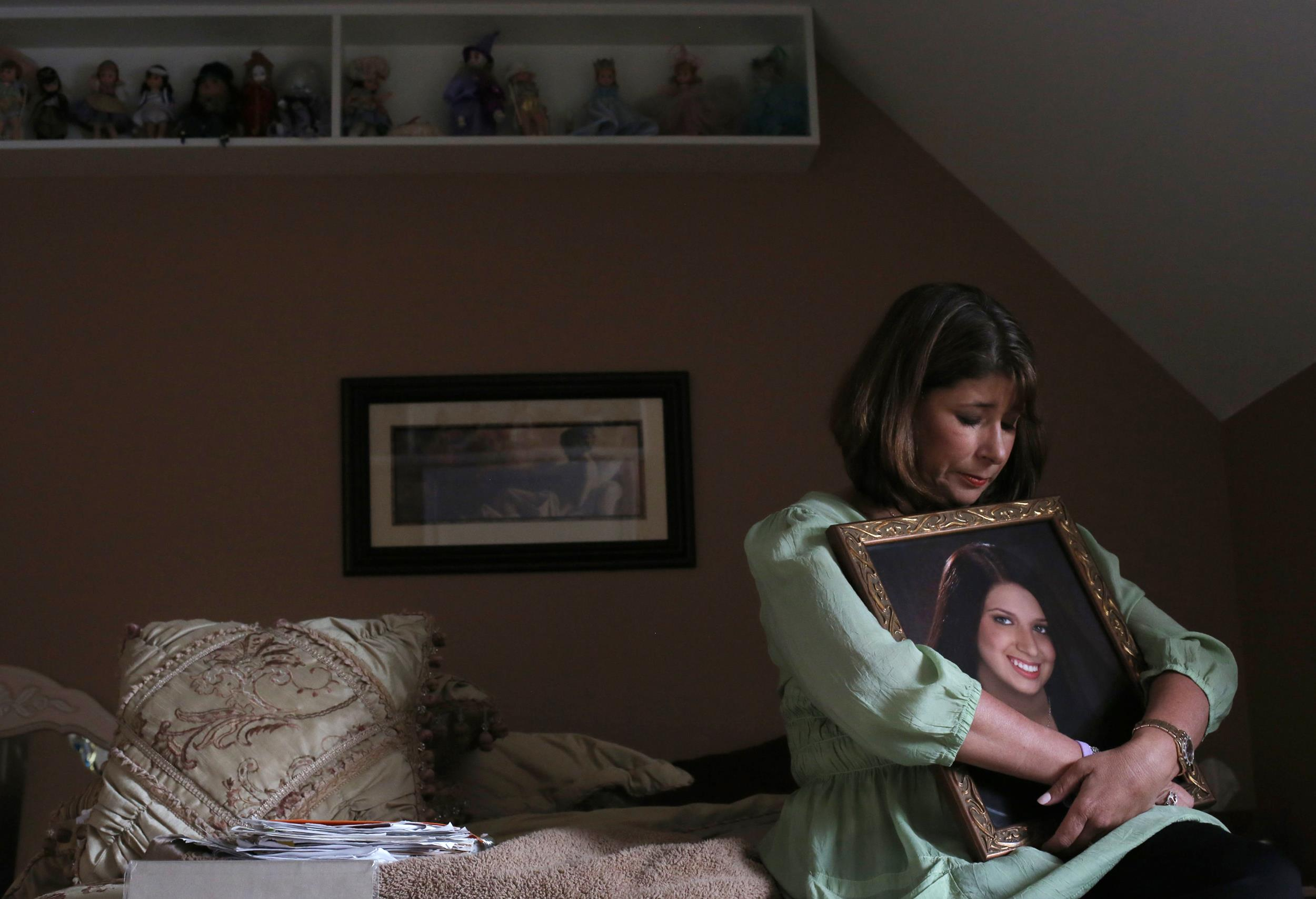 Image: Alicia Stillman holds a portrait of her 19-year-old daughter, Emily, who died in February 2013 from meningitis B.
