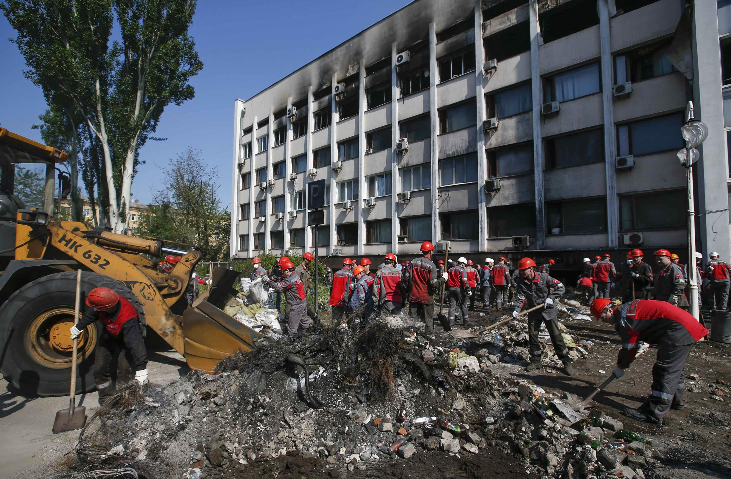 Image: Workers of Metinvest, majority-owned by Rinat Akhmetov's System Capital Management, remove barricades and debris in front of the City Hall in Mariupol