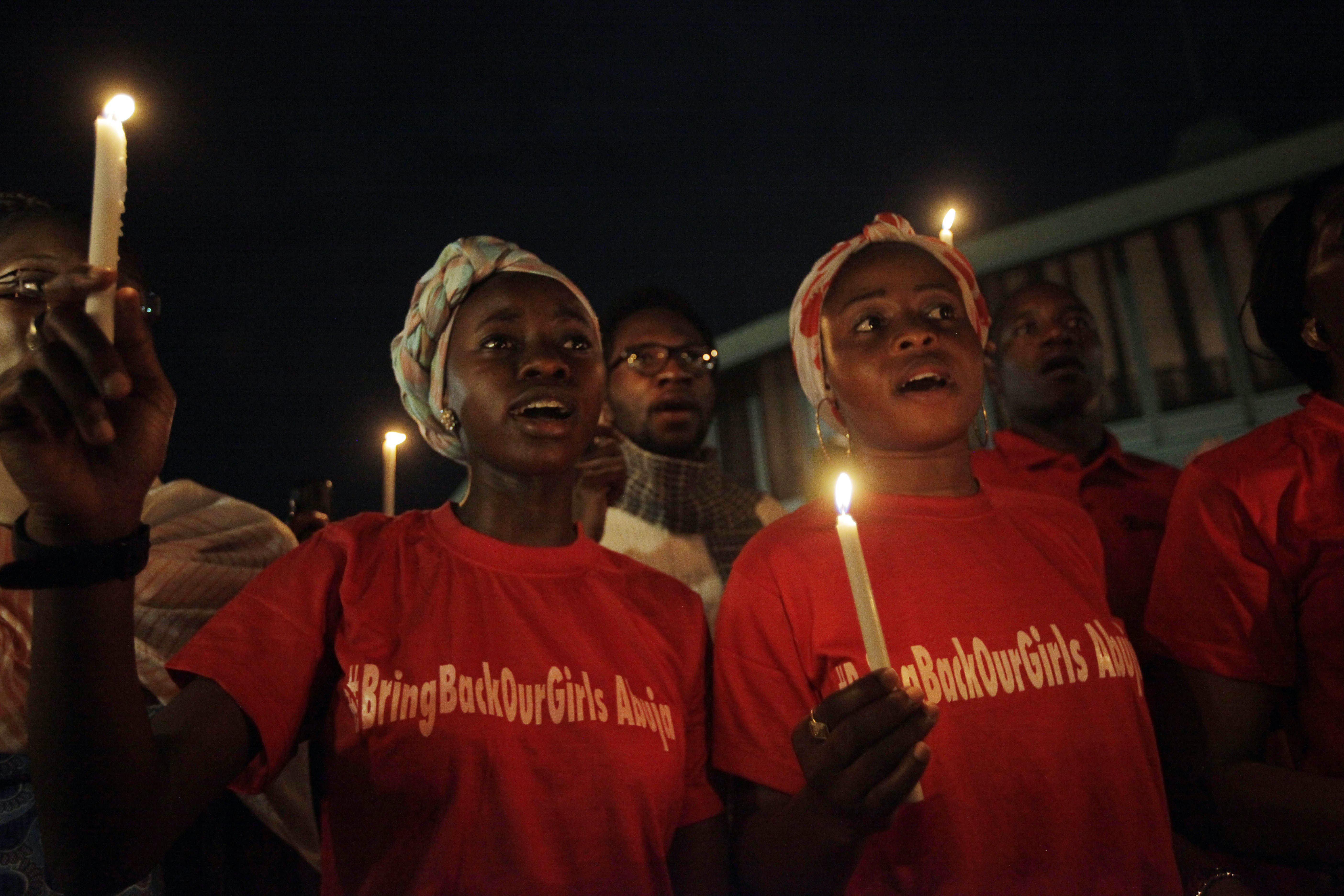 Image: People hold candle light during a vigil to mark one month after the girls were kidnapped, in Abuja, Nigeria, Wednesday, May 14, 2014.