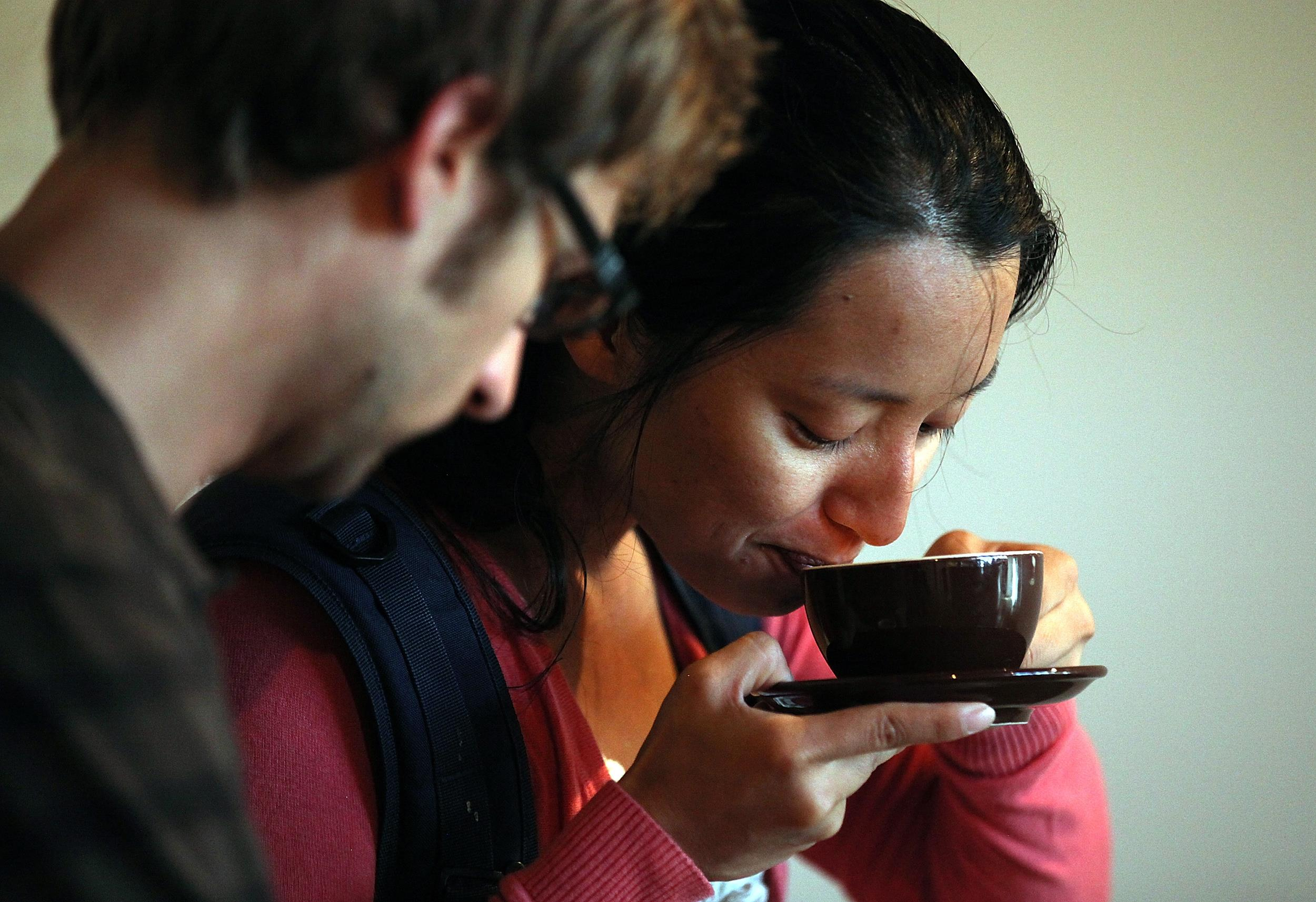 Image: A woman sips a cup of coffee.