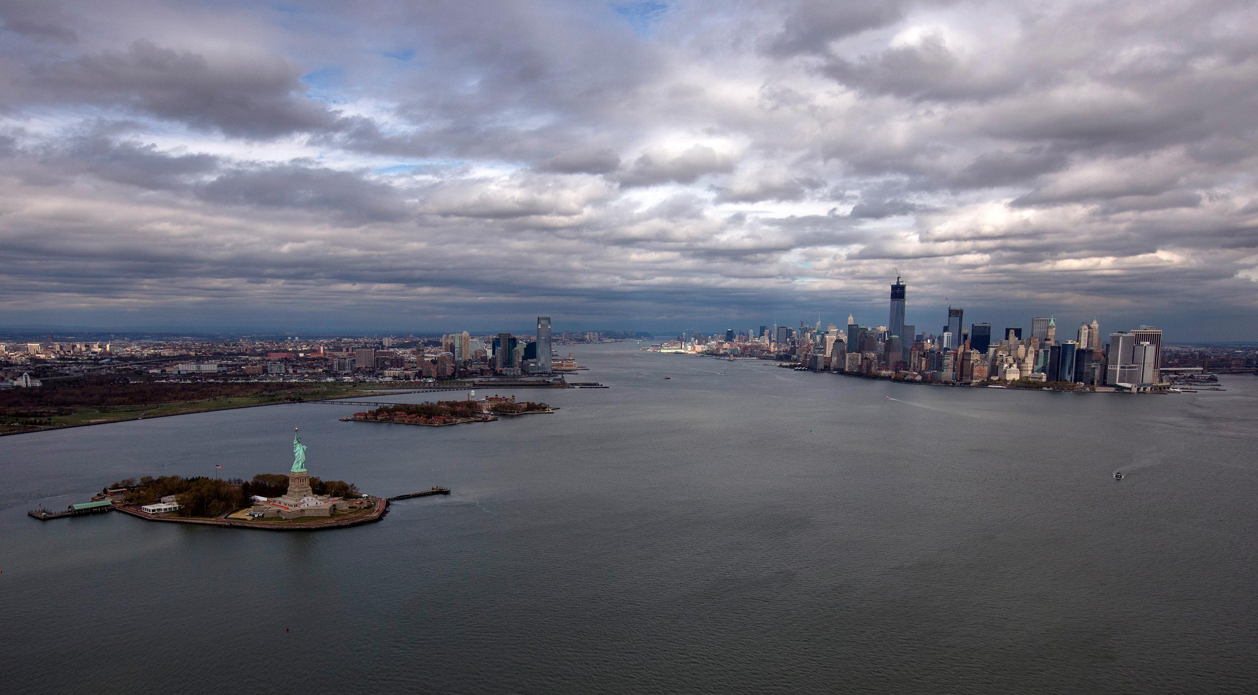 Image: The Statue of Liberty, Liberty Island and Ellis Islands are seen to the left next to New York's Lower Manhattan skyline