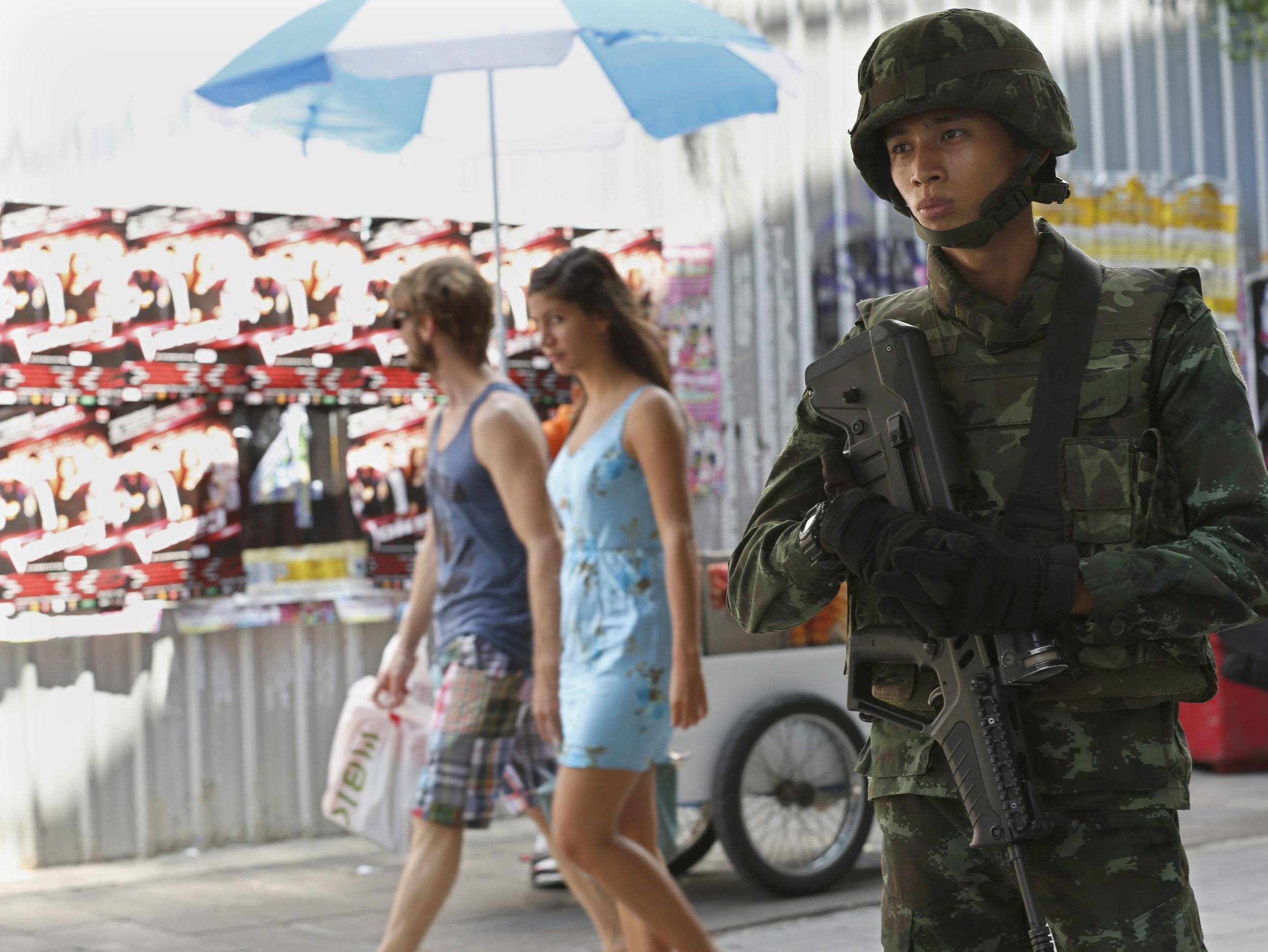 Image: A foreign tourist couple walks behind a Thai soldier guarding in a street in Bangkok, Thailand, May 21.