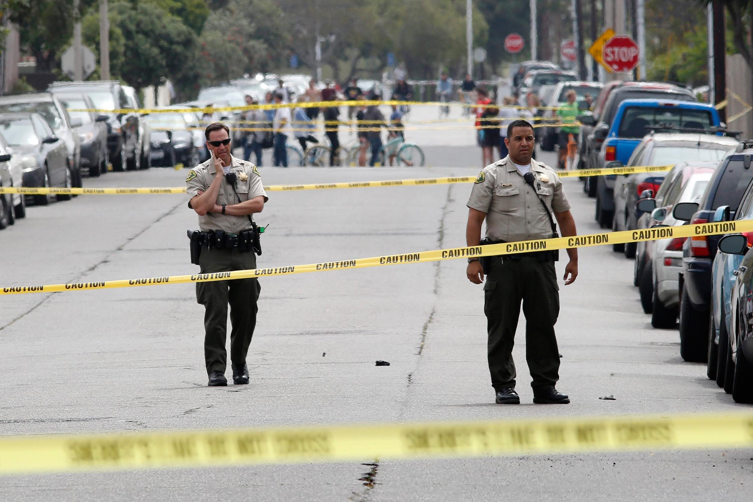 Image: Santa Barbara sheriff deputies stand in the street at one of nine crime scenes after series of drive-by shootings