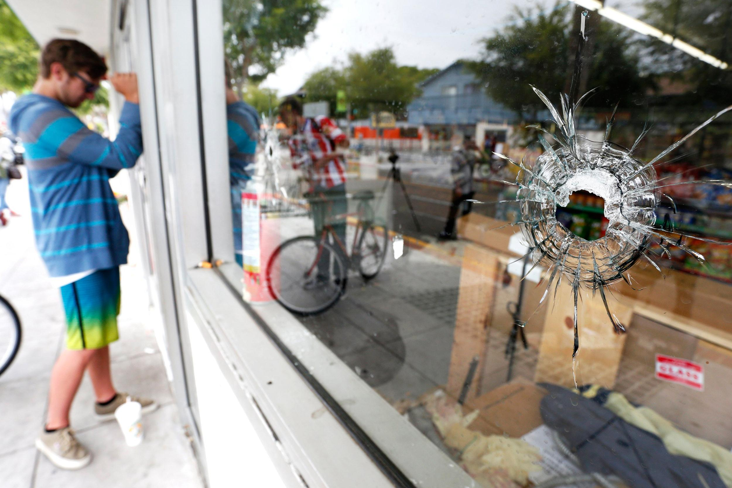 Image: A man looks through a window with bullet holes at a deli