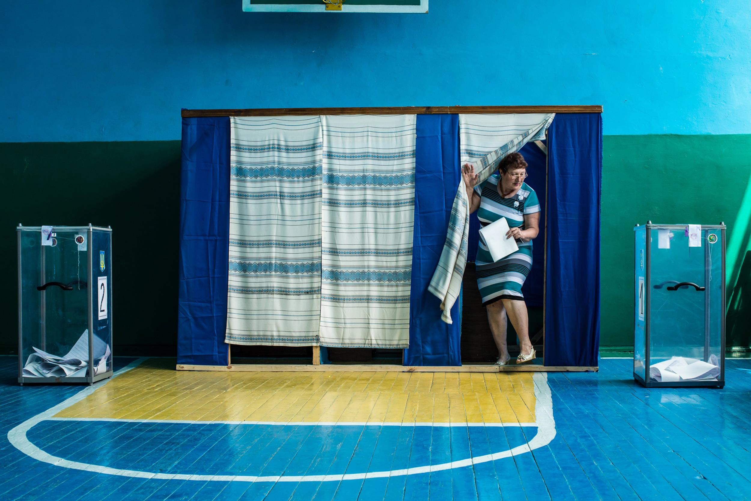 Image: A woman at a polling station emerges from a voting booth after filling out her ballot in Ukraine's presidential election