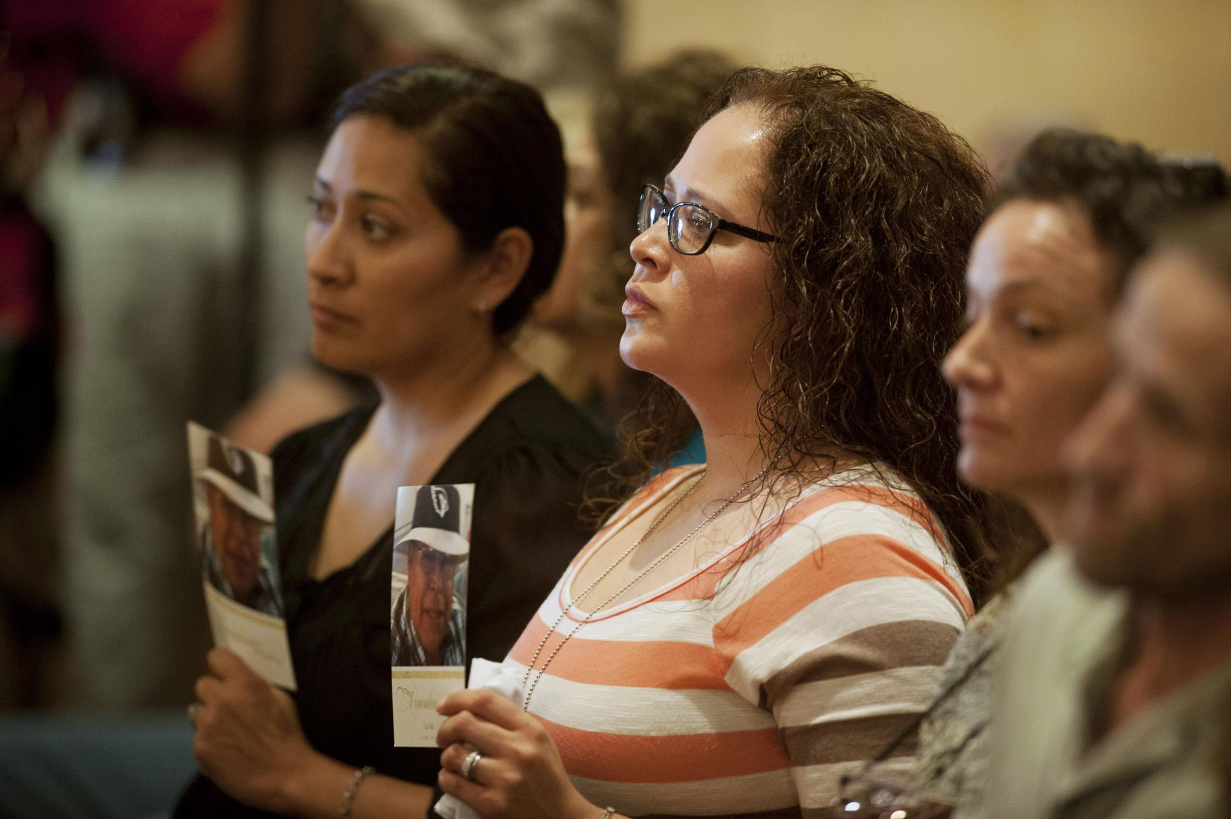Image: Dana Valle and Stacy Acevedo hold pictures of their father Cecil Valle at a forum at the Burton Barr Central Library on May 9, 2014 in Phoenix, Arizona.