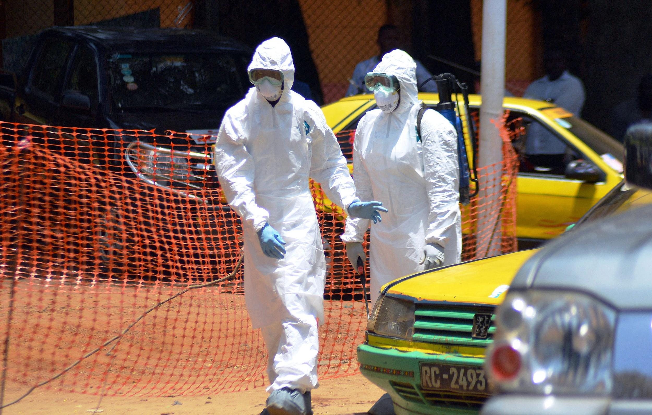 Image: Two members of the Guinean Red Cross, in protective gear, arrive on March 31, 2014 to evacuate the bodies of two people who died from the Ebola virus