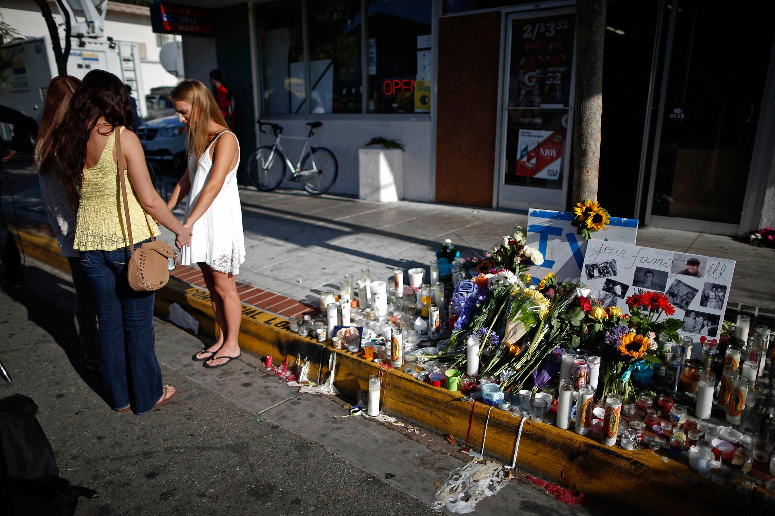 Image: Women pray in front of a makeshift memorial for UCSB student Christopher Michael-Martinez in Isla Vista