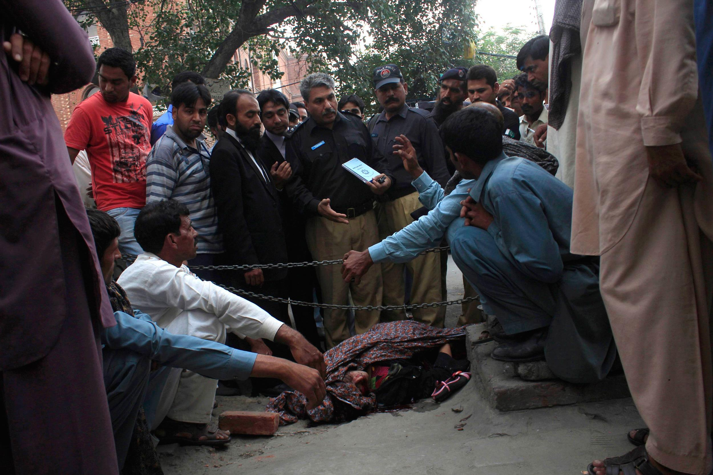 Image: Police collect evidence near body of Farzana Iqbal, killed by family members, at site near Lahore High Court building in Lahore