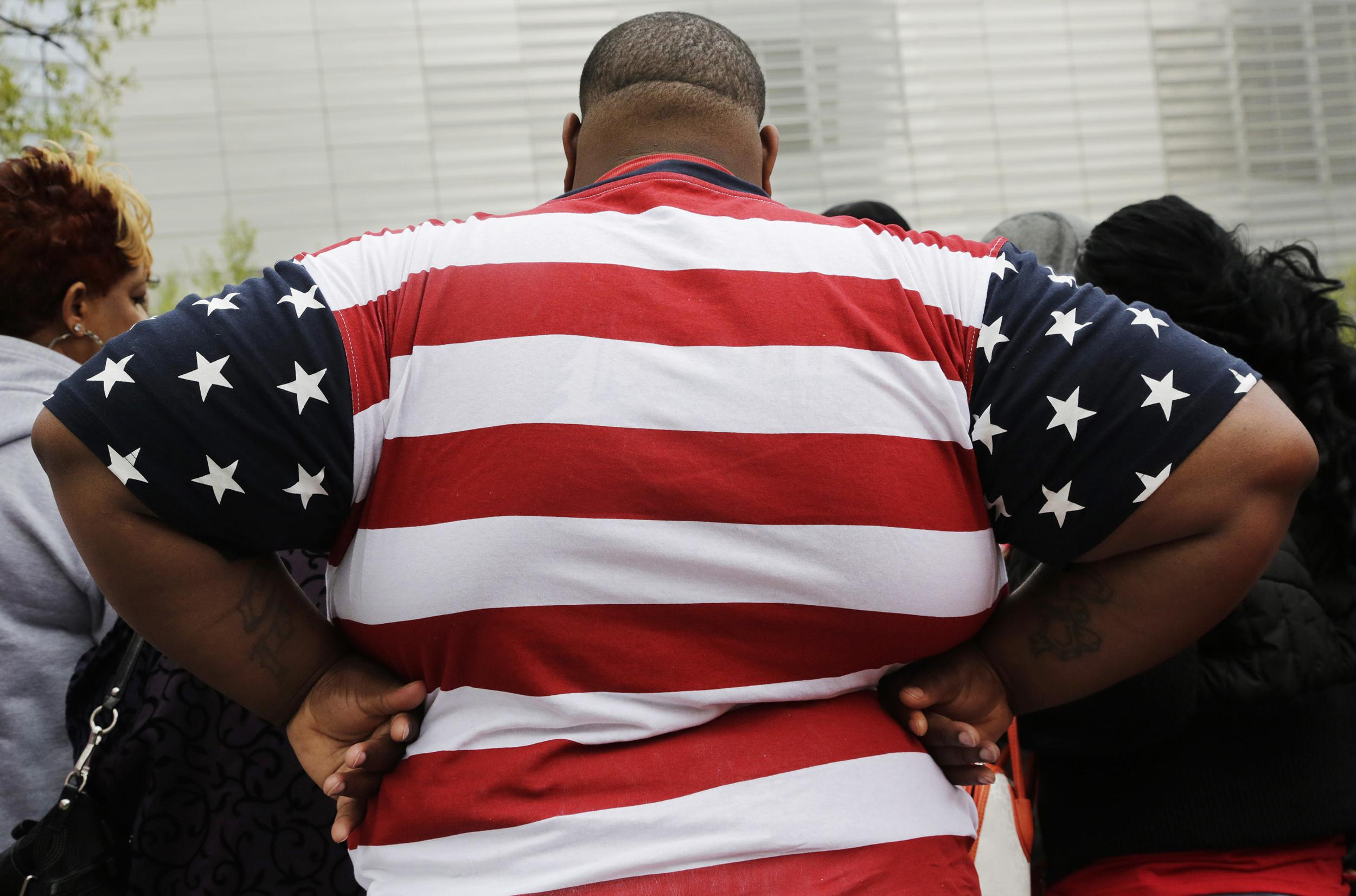 Image: An overweight man wears a shirt patterned after the American flag
