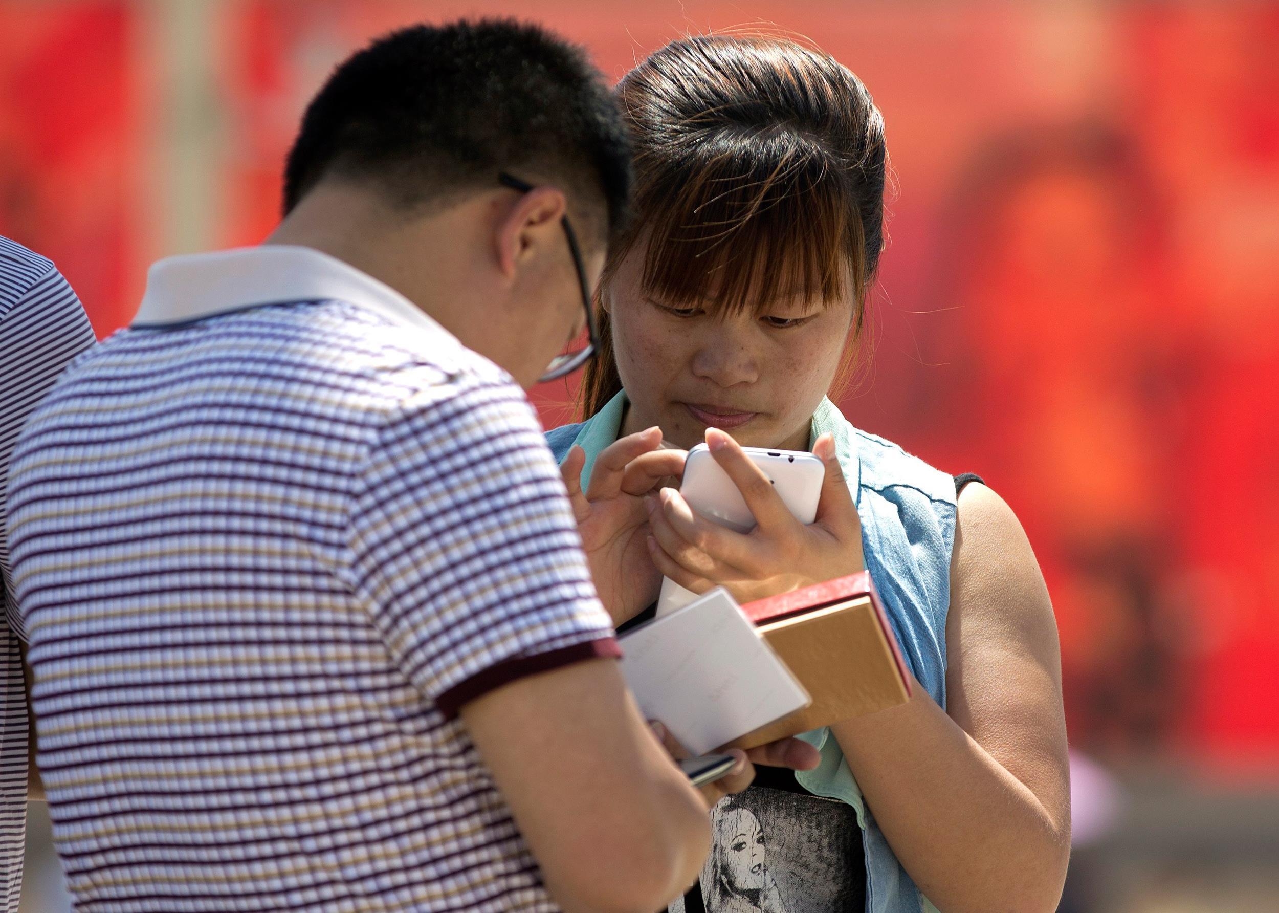 Image: People use smartphones on Tiananmen Square in Beijing