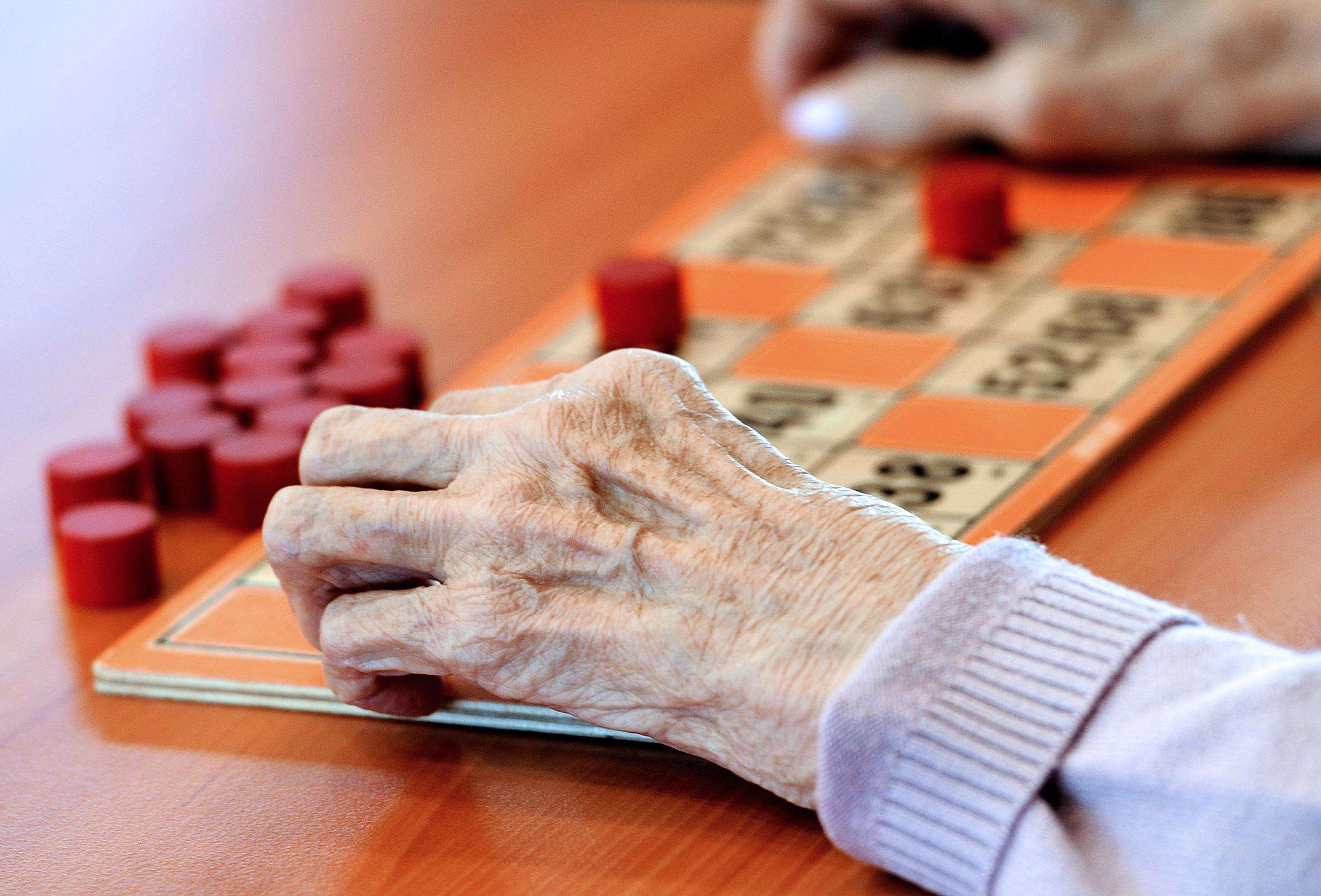 Image: An elderly woman plays bingo.
