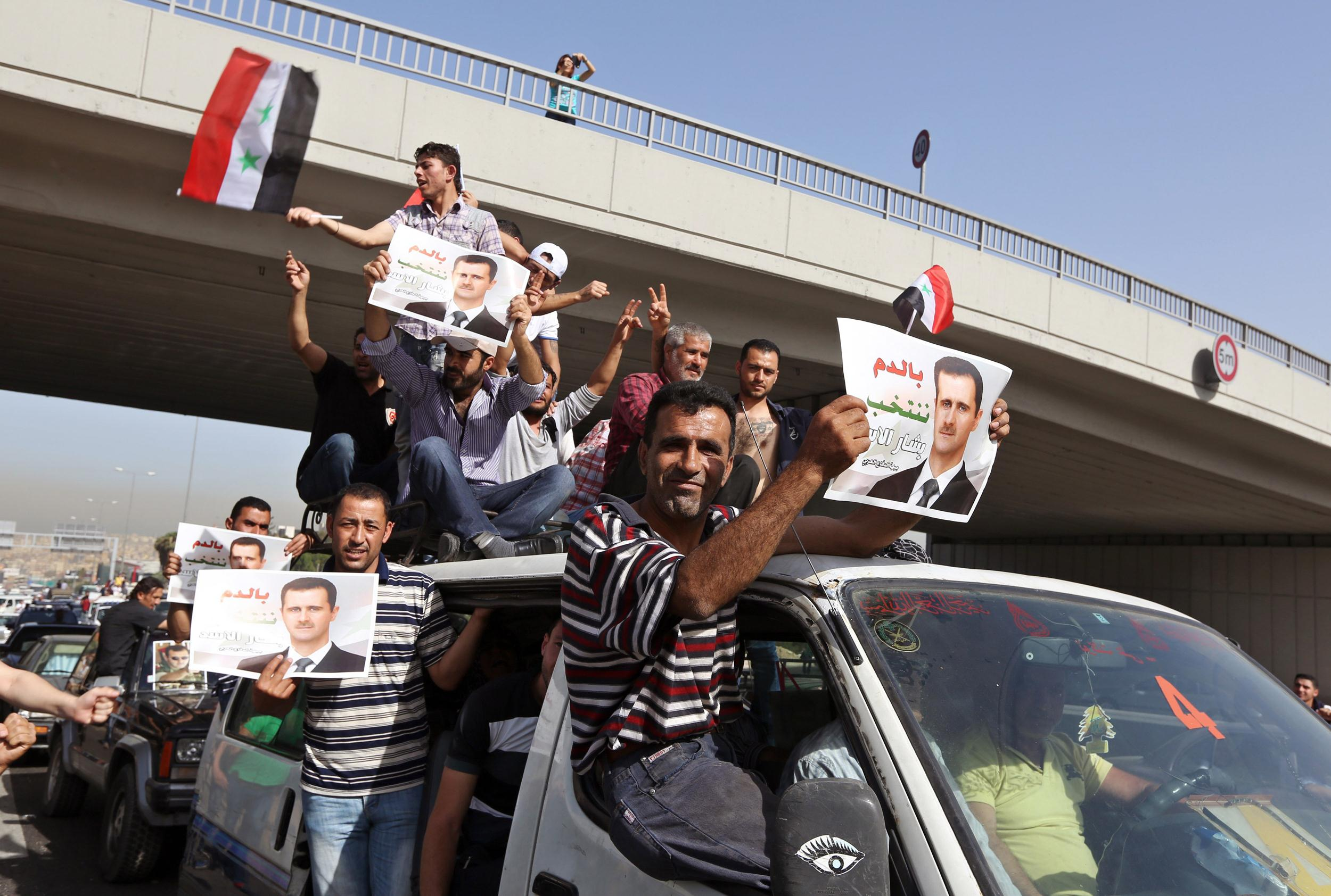 Image: Syrians who live in Lebanon carry portraits of Syrian President Bashar Assad and their national flags as they drive towards to the Syrian embassy to vote in the presidential election in Yarze, east of Beirut, Lebanon, Wednesday, May 28, 2014.