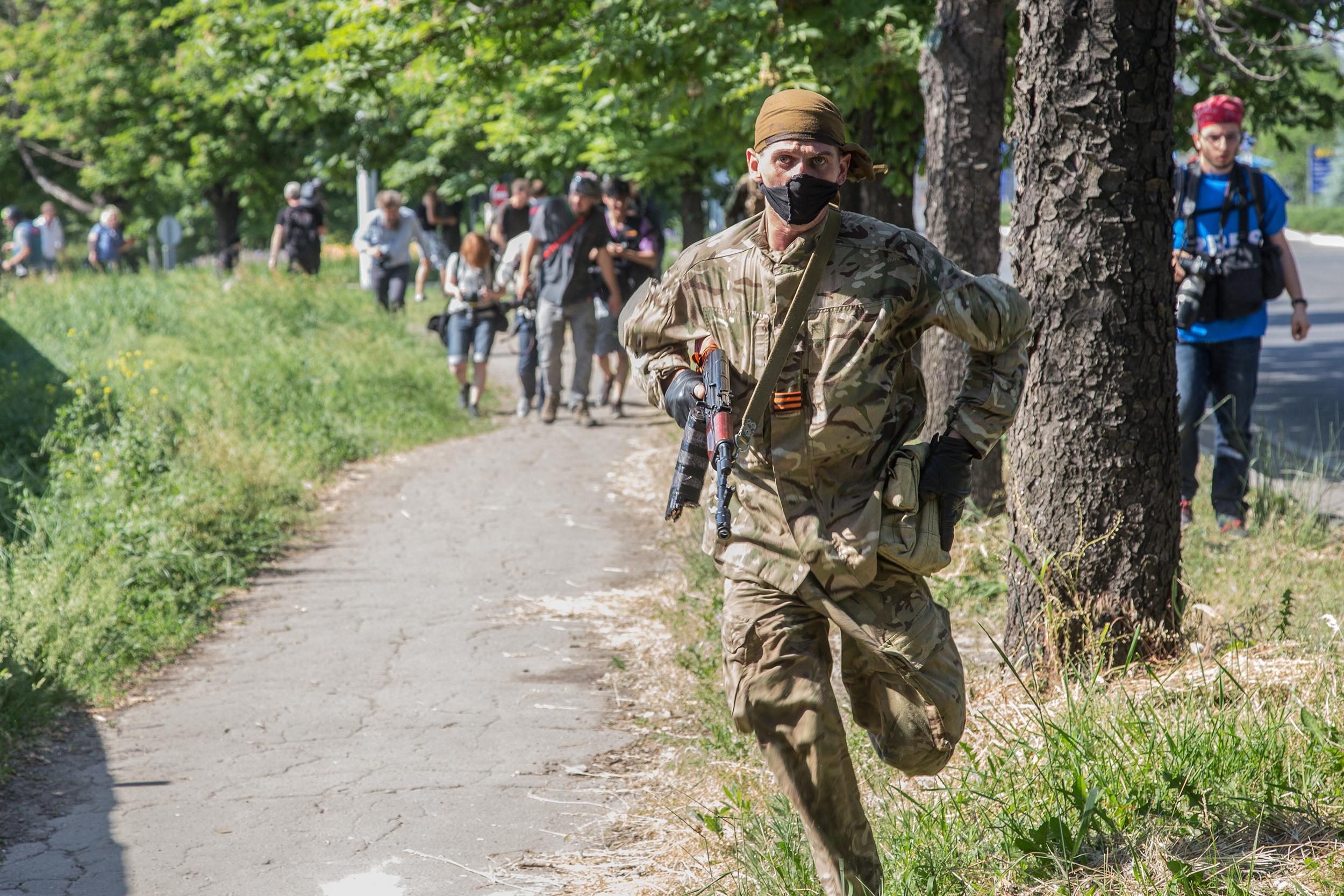 Image: A separatist combatant gets himself to safety during the fighting at Donetsk airport in Donetsk