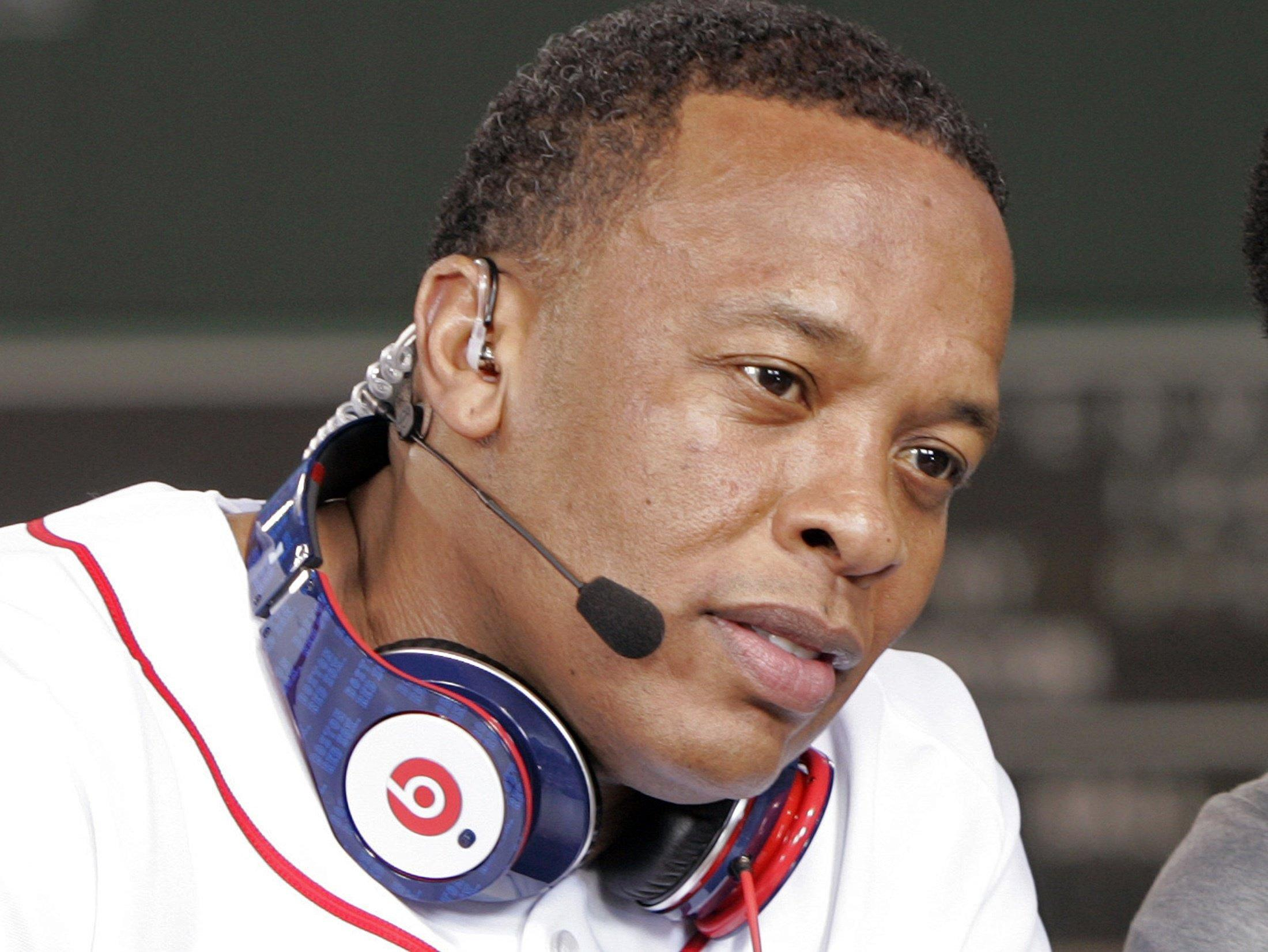 Recording artist Dr. Dre wears a pair of Beats headphones as he attends the MLB 2010 season opener in Boston.