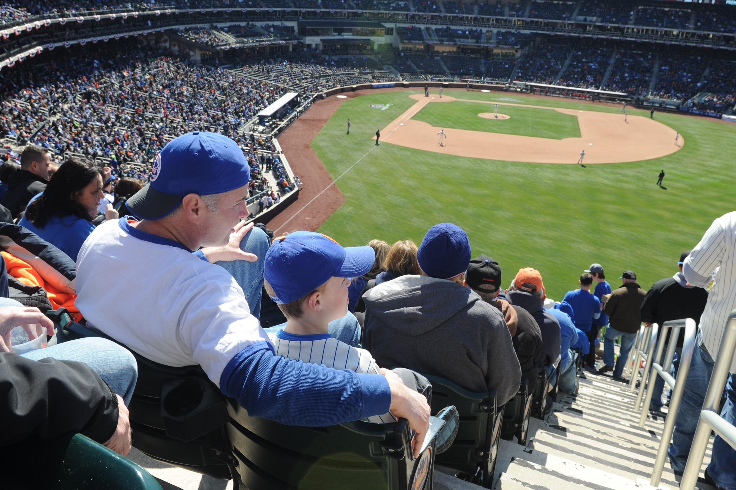 Image: A father and his son watch an Opening Day game between the New York Mets and the Washington Nationals