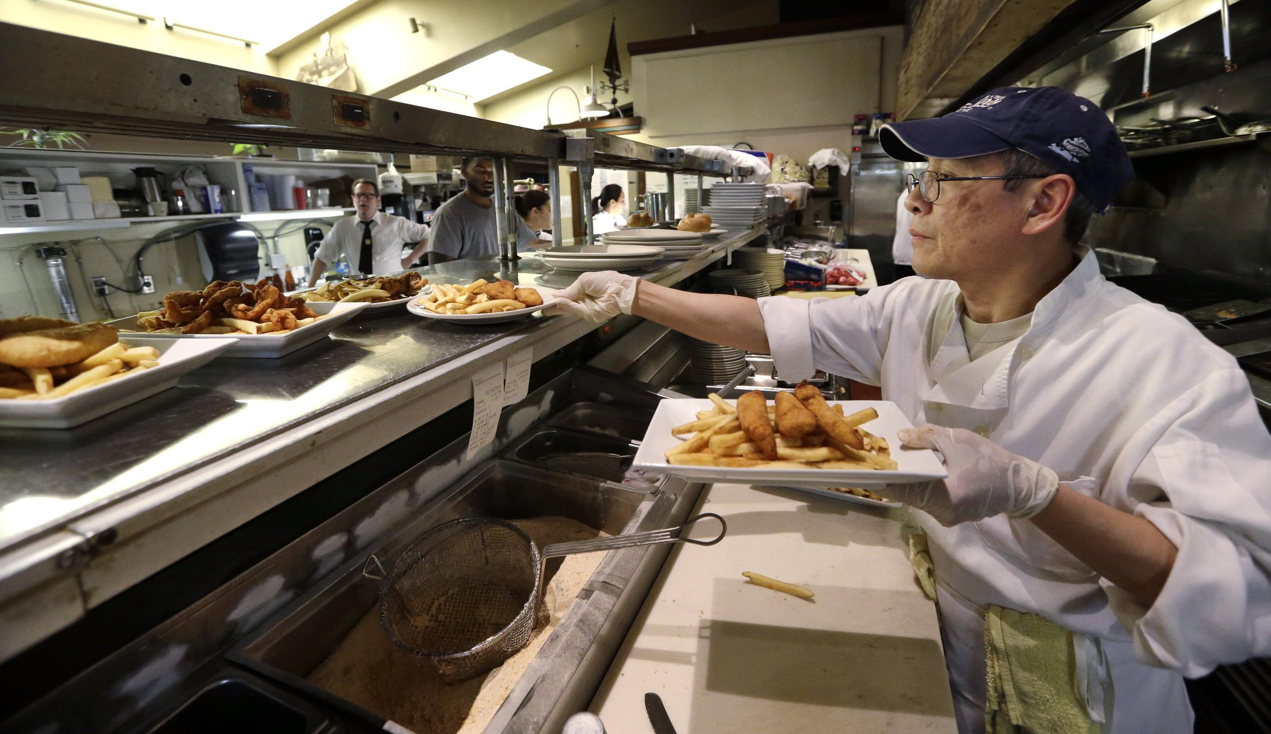 Image: Seattle cook Sam Woo puts up orders at Ivar's Acres of Clams.