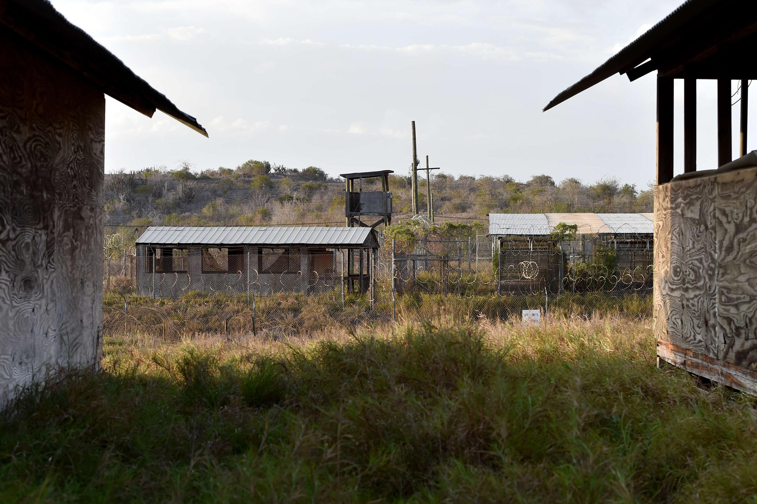 Image: The razor wire-topped fence and a watch tower at the abandoned
