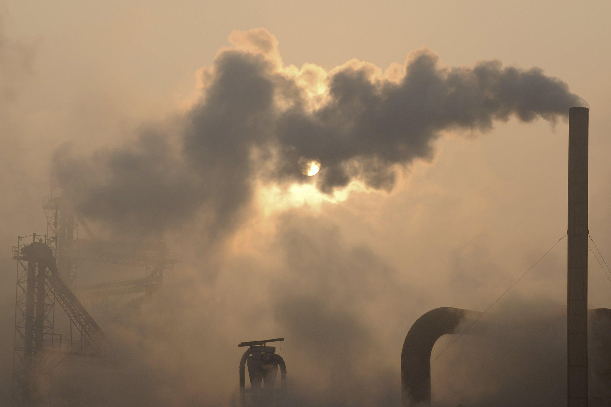 Image: Smoke rises from the chimneys of a cement plant in eastern China's Shandong province in 2013.