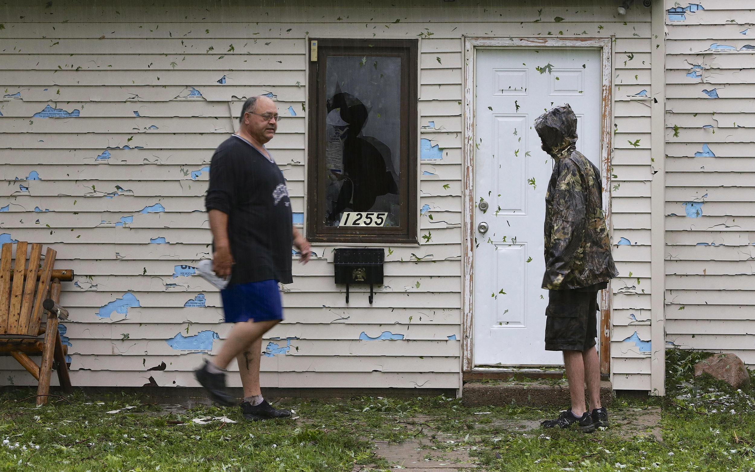 Image: Blair residents survey hail damage in the pouring rain following a severe thunderstorm in Blair, Neb.