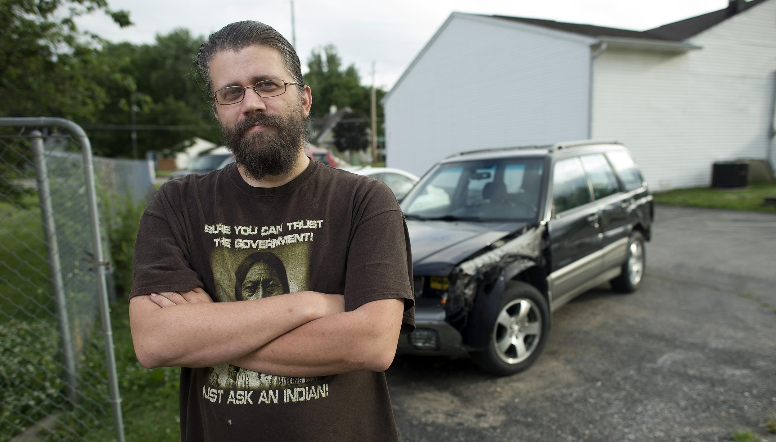 Image: Erick Penny of Indianapolis, Ind., stands in front of his car, which he needs to get to work