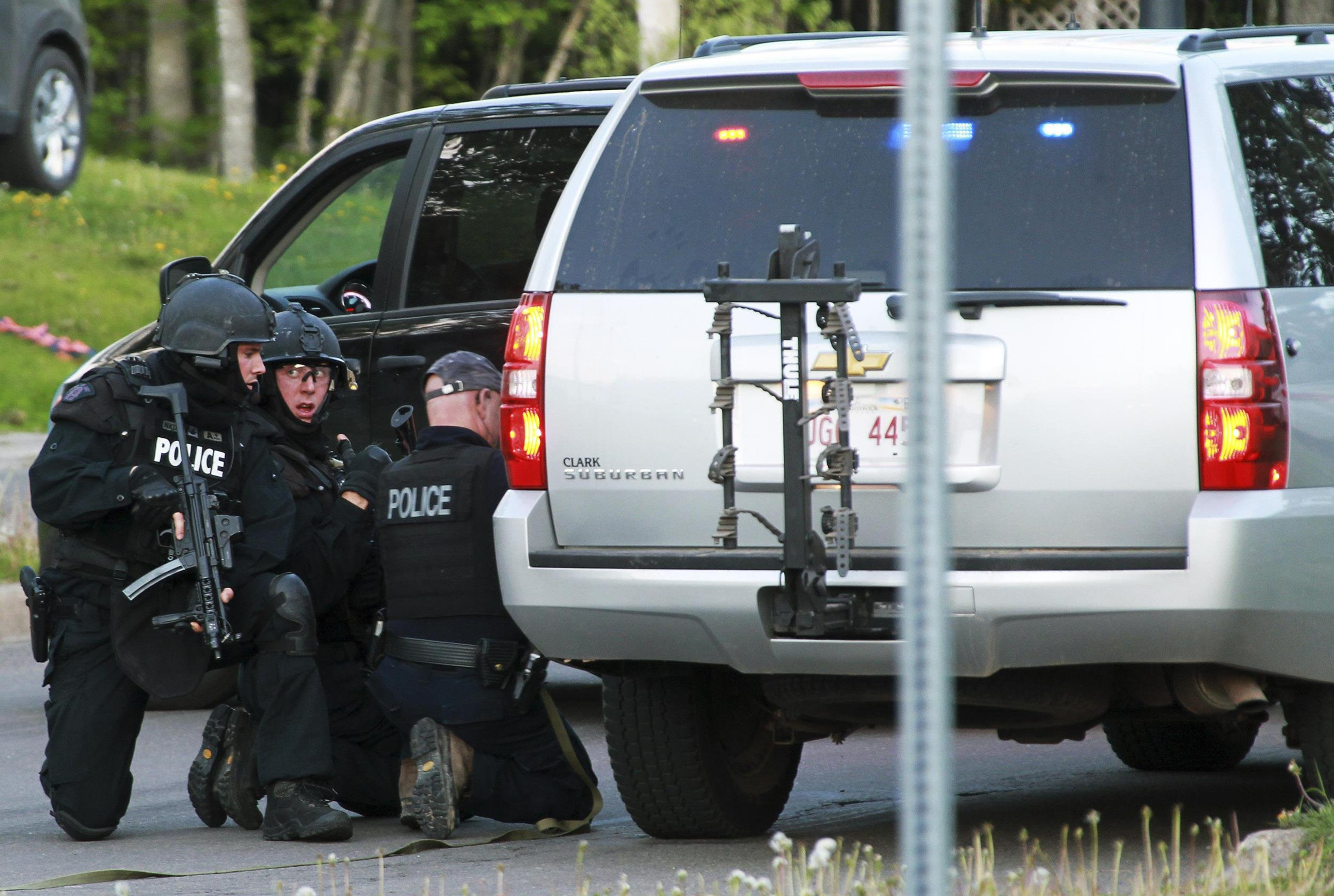 Image: Emergency Response team members take cover behind vehicles in Moncton, New Brunswick