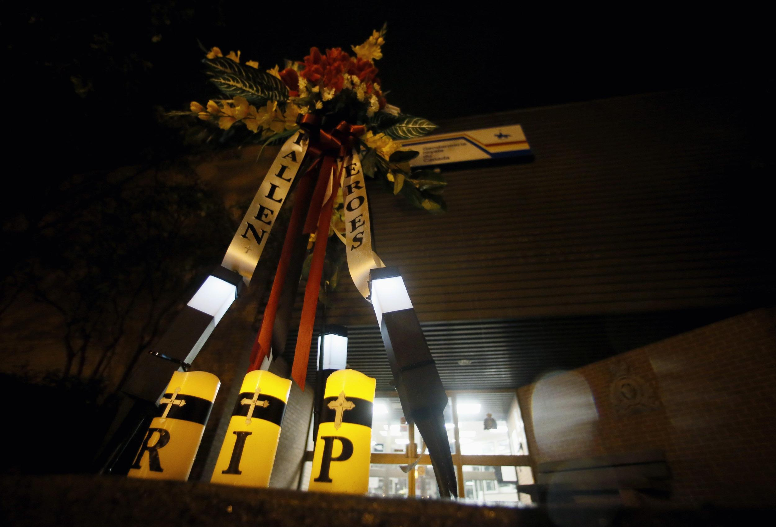 Image: Flowers and candles at the RCMP station in Moncton