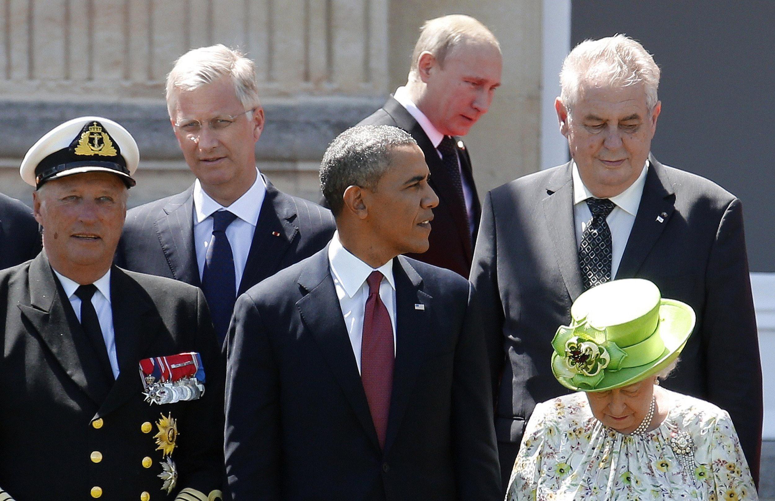 Image: Russian President Vladimir Putin passes behind President Barack Obama