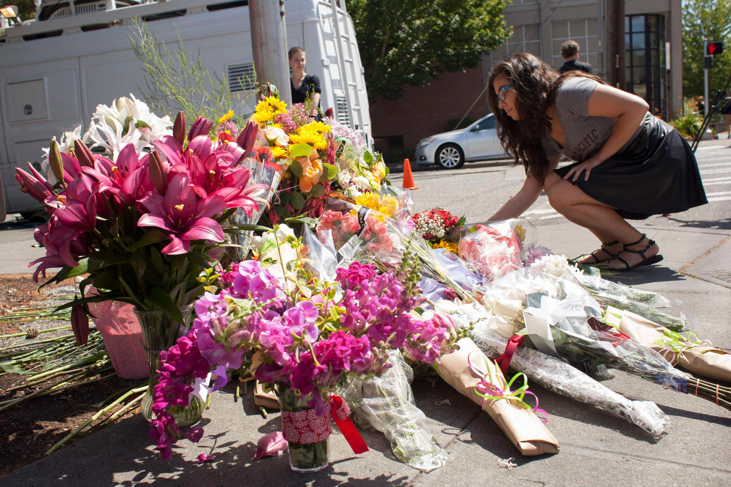 Image: Student places a bouquet of flowers at a memorial on the Seattle Pacific University campus in Seattle