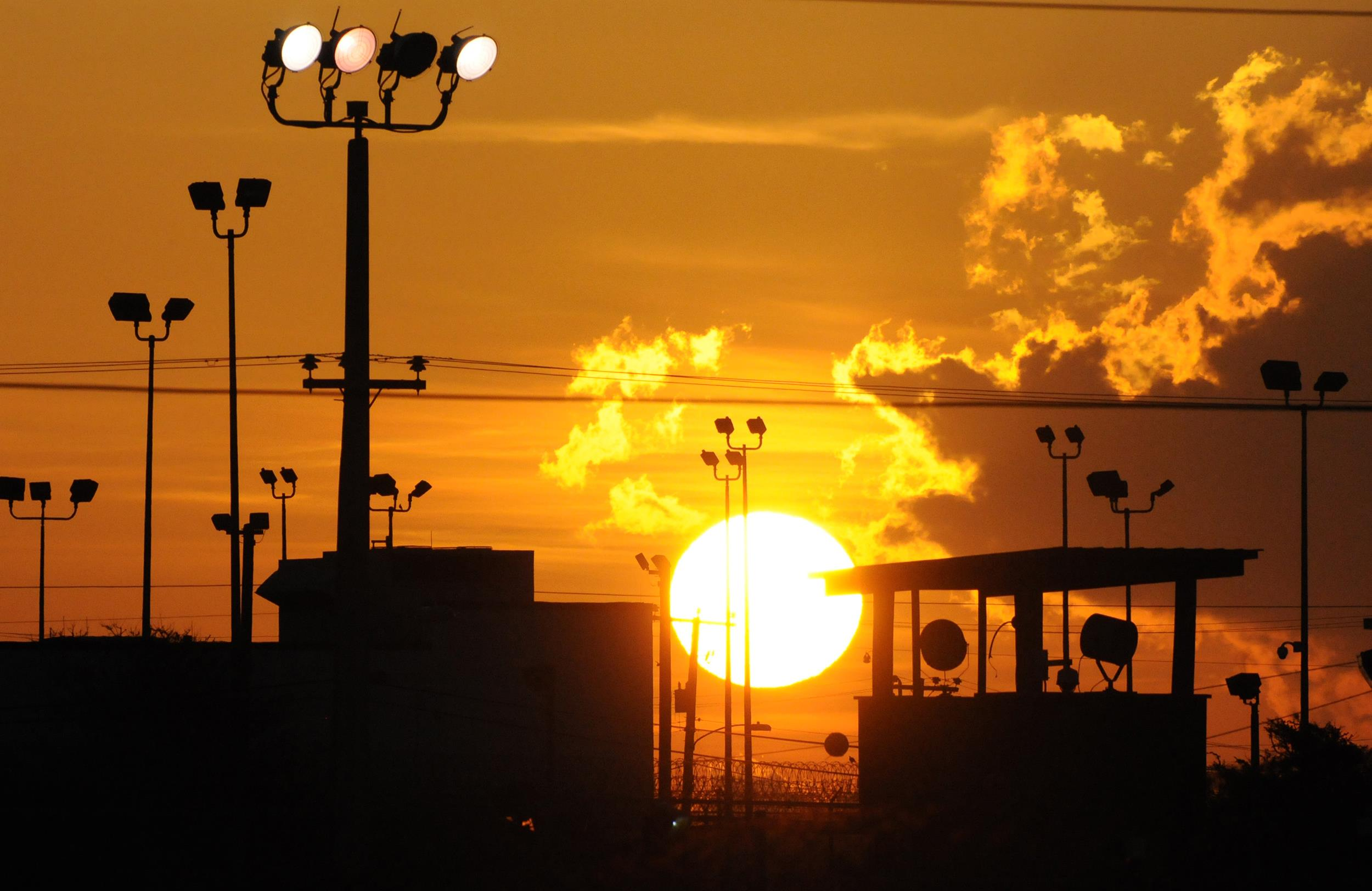 Image: towers overlooking a U.S. detention facility are silhouetted against a morning sunrise at Guantanamo Bay U.S. Naval Base, Cuba, in 2012