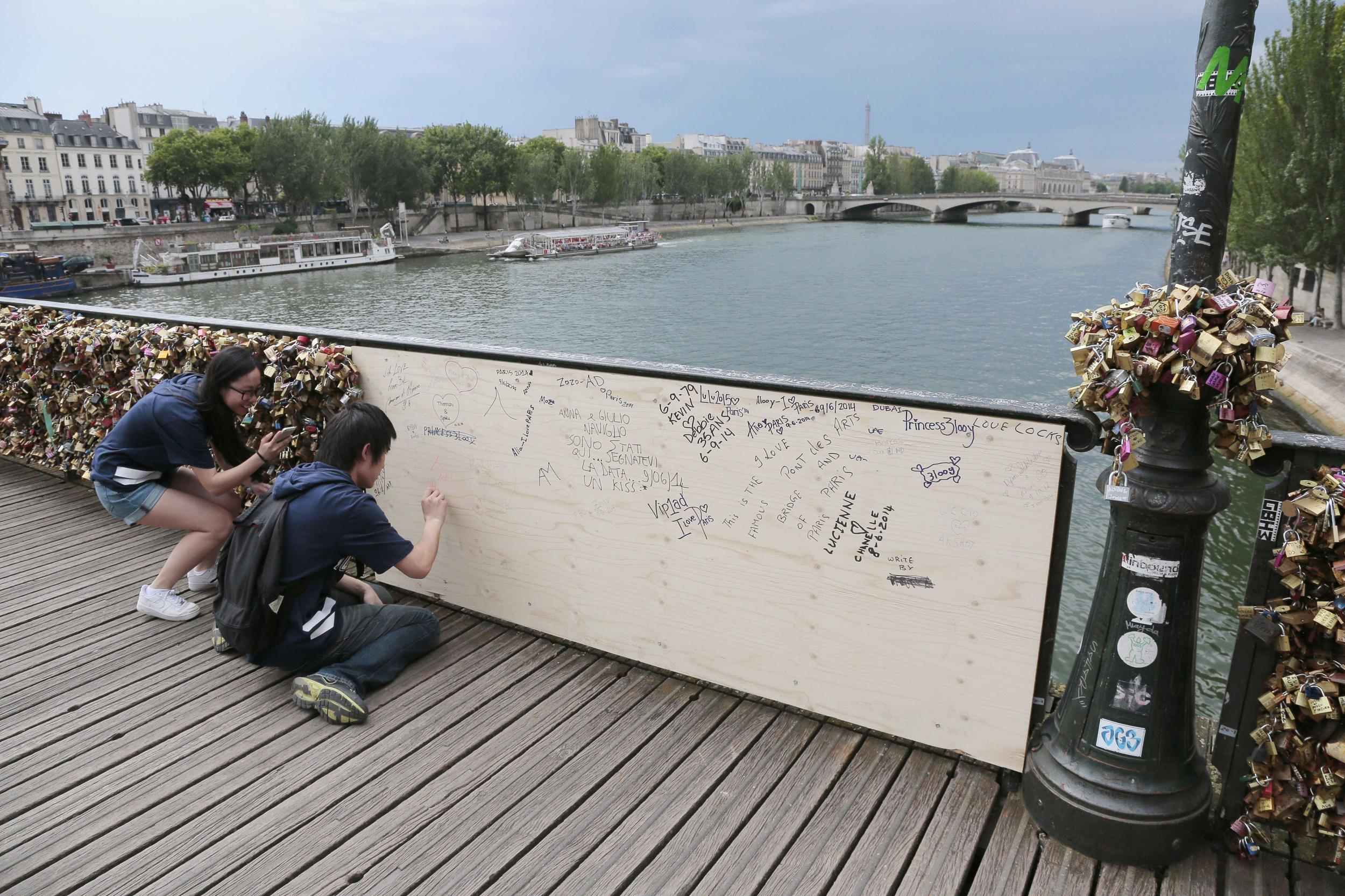 Image: People write inscriptions onto a wooden panel on the Pont des Arts bridge