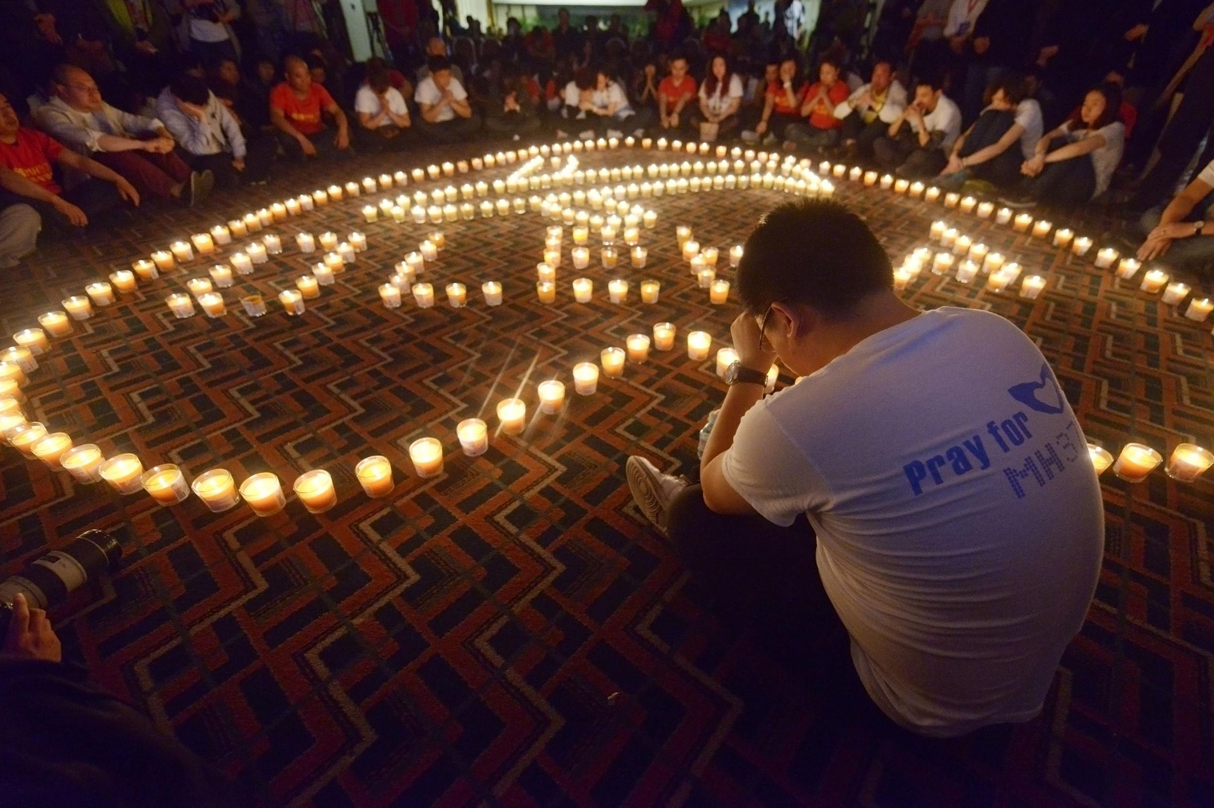 Image: A Chinese relative of passengers on Malaysia Airlines flight MH370 prays in front of candles as he takes part in a prayer service at the Metro Park Hotel