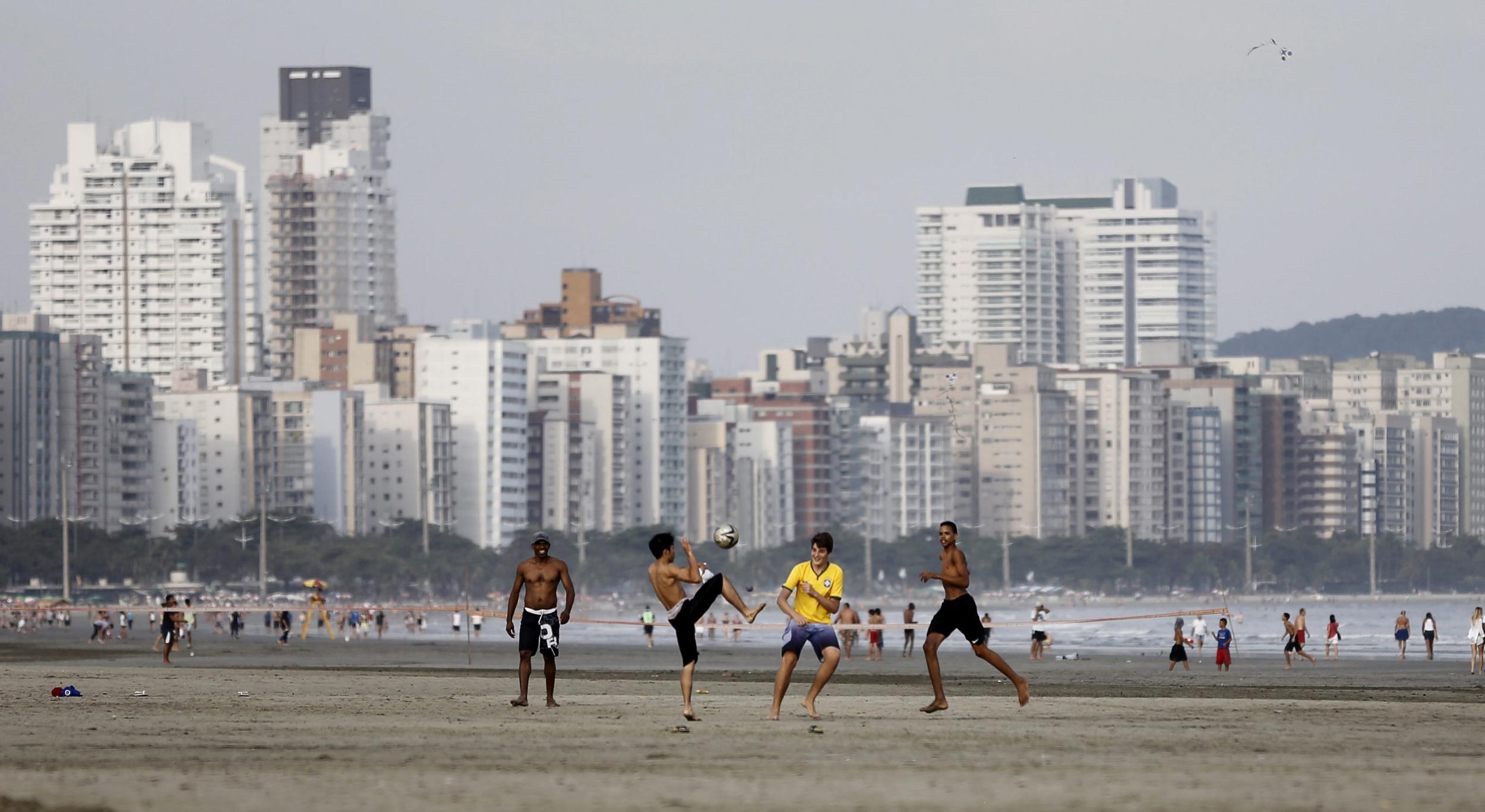 Image: Brazilian teenagers play soccer at a beach in Guaruja near Sao Paulo