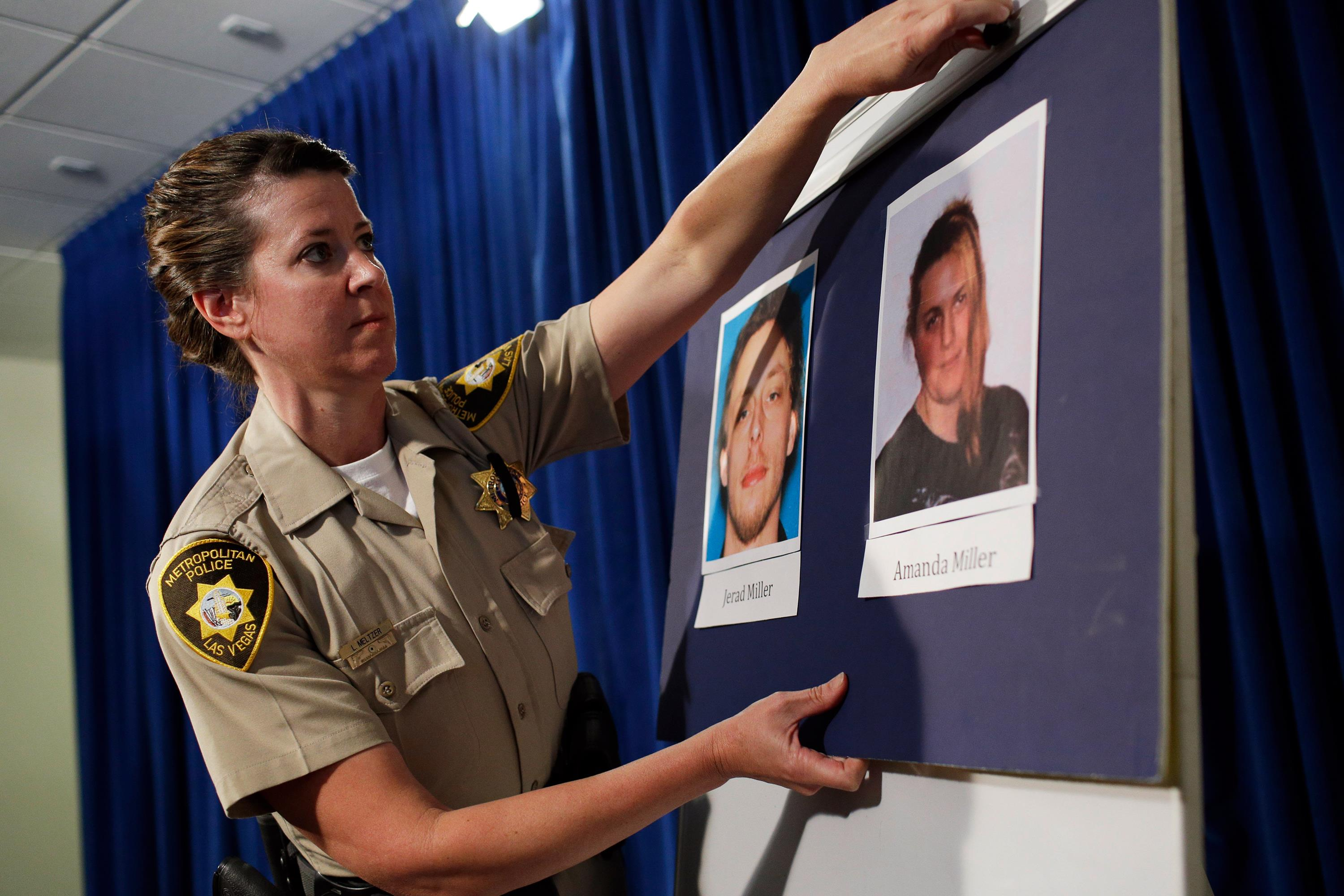 Image:Las Vegas Metropolitan Police Department Officer Laura Meltzer hangs up pictures of suspects Jerad Miller and Amanda Miller before a news conference