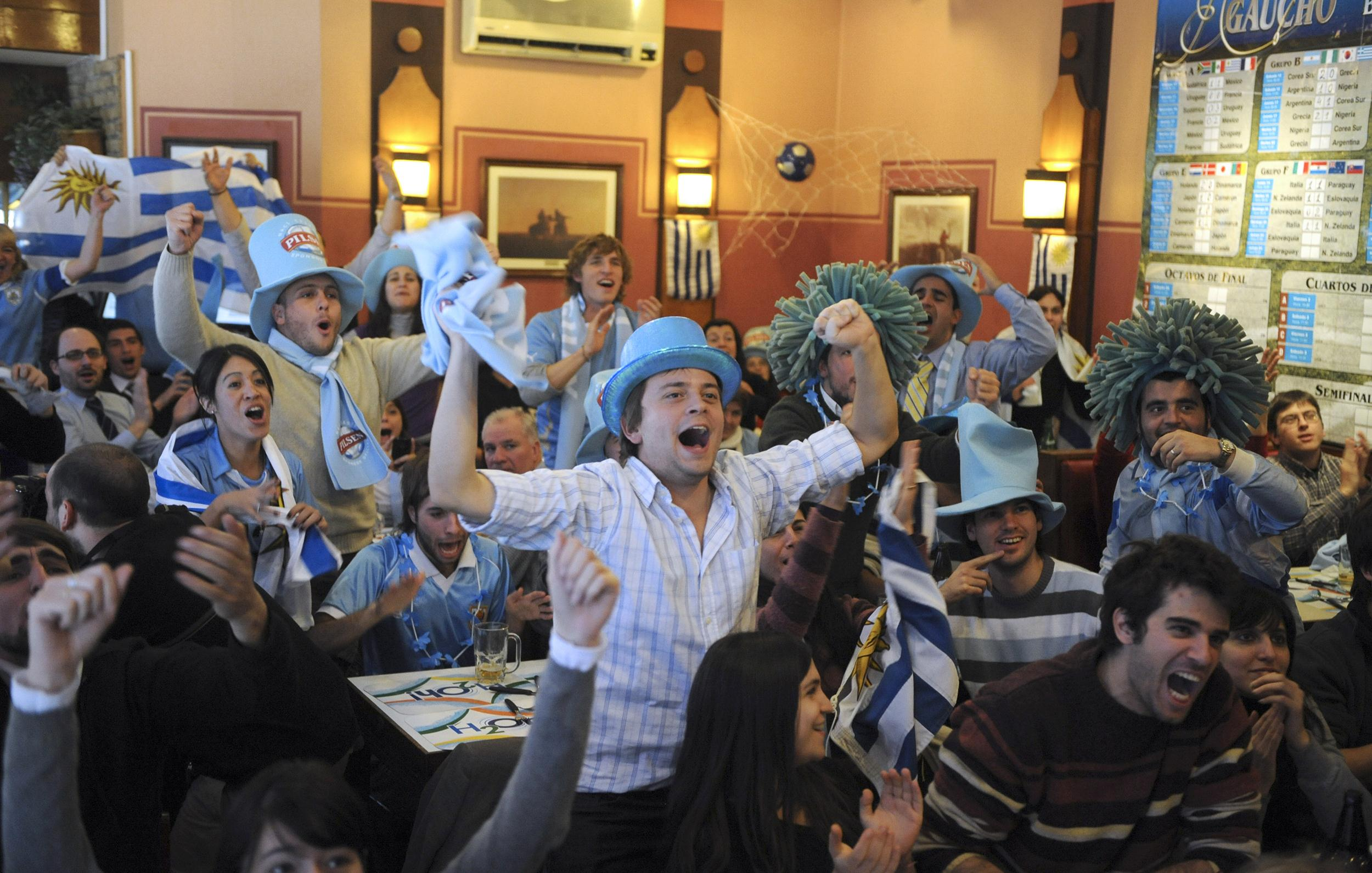 Image: Uruguayan football fans celebrate the first goal of their team in the FIFA World Cup 2010 match against Mexico, at a bar in downtown Montevideo
