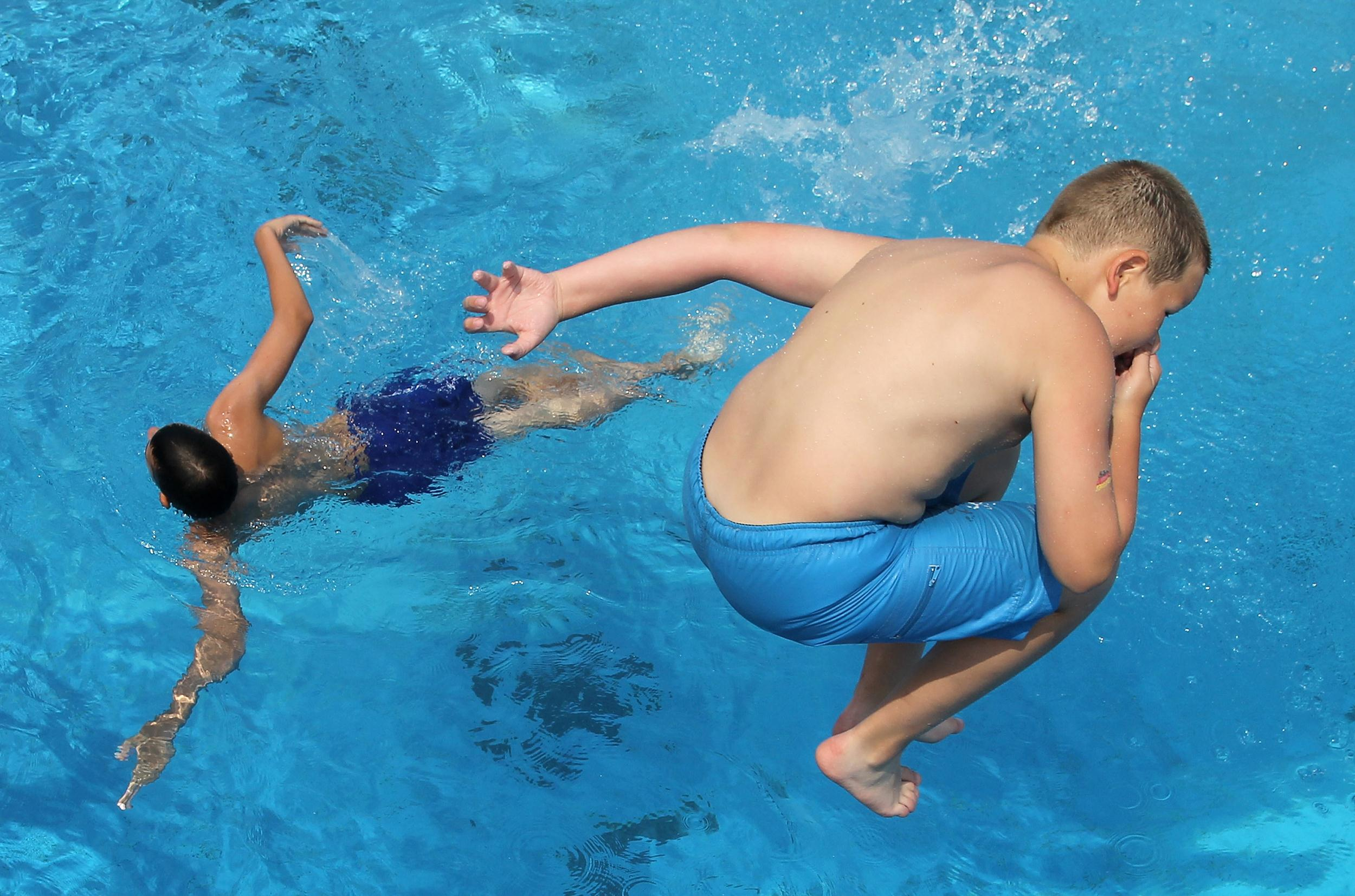 Image: Children jump from a diving board at a public pool