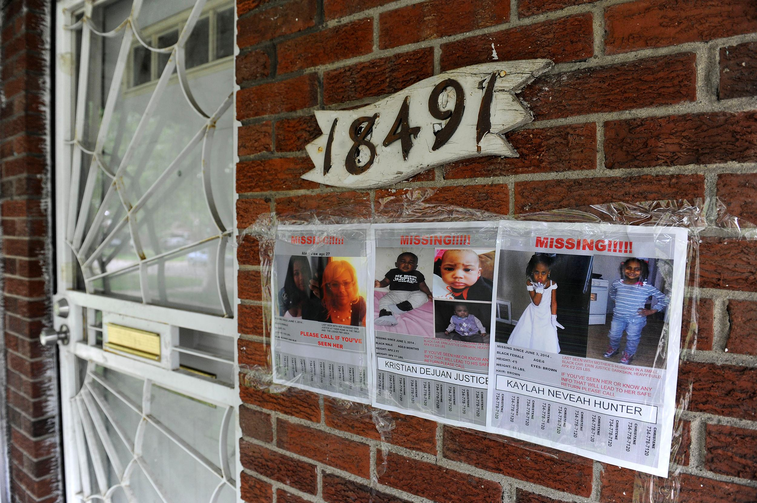 Image: Flyers of a missing woman and children are taped to the brick home of Alicia Fox