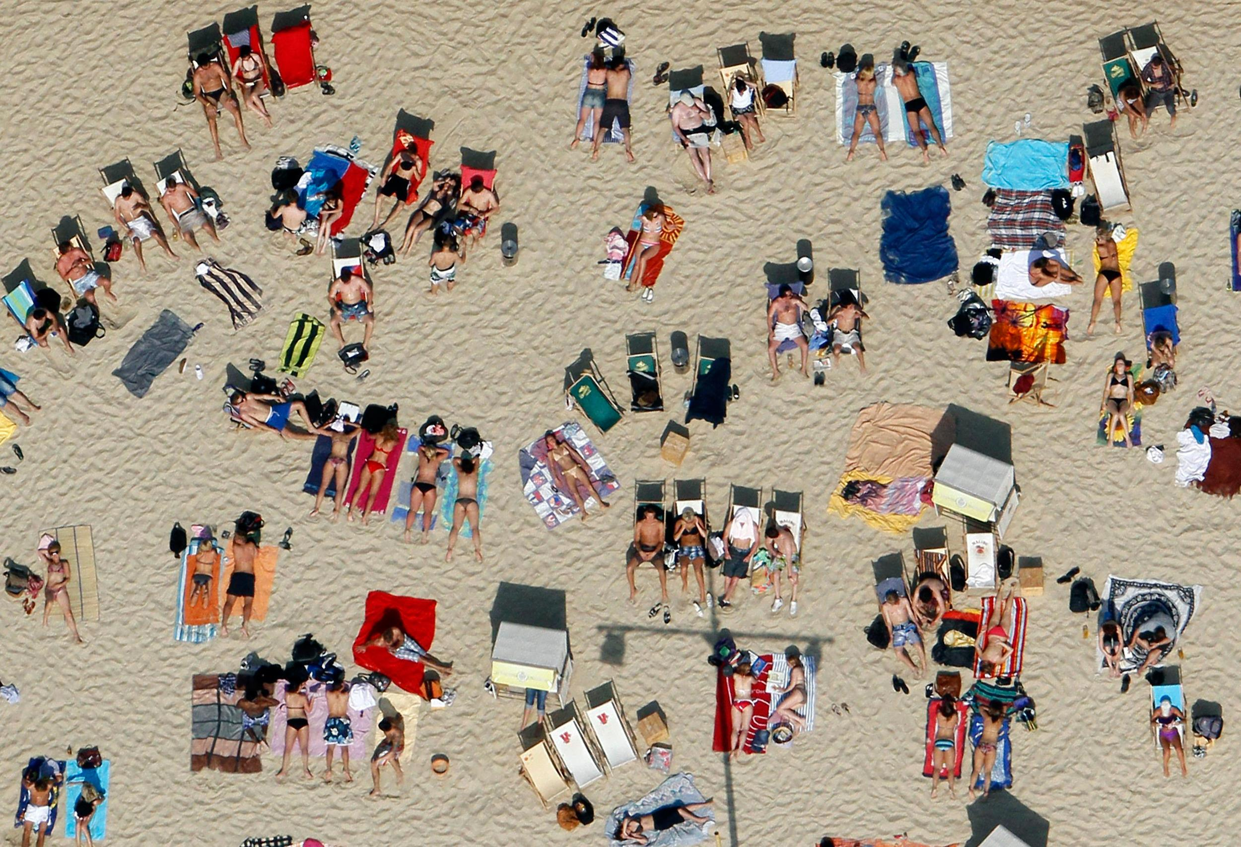 Image: Sunbathers lay in the sun at the