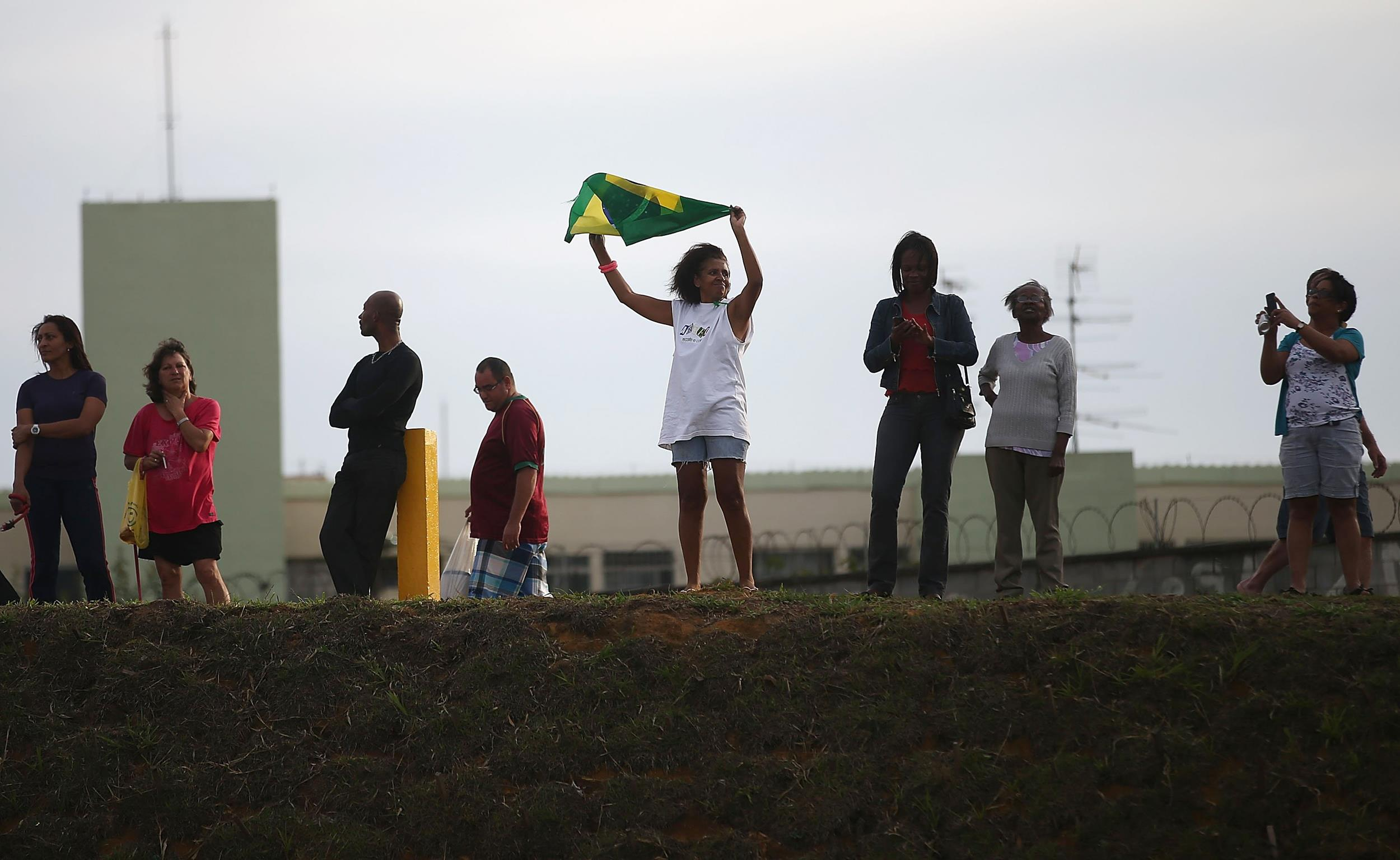 Image: A woman waves a Brazilian flag outside Itaquerao stadium