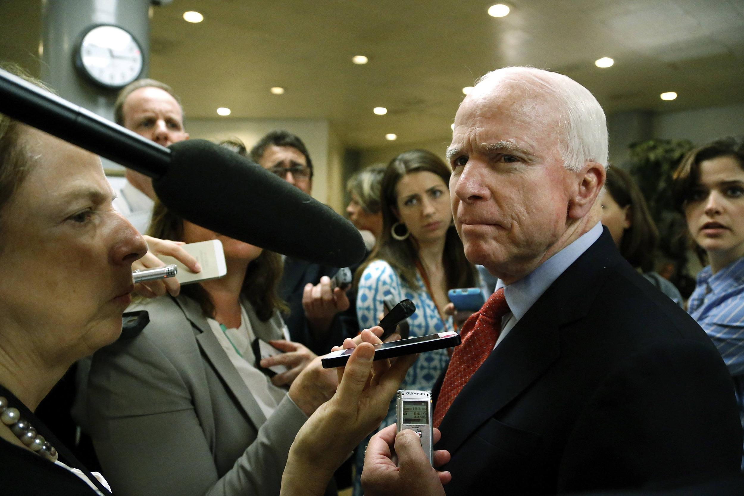 Image: McCain talks to reporters after a closed-door Senate Armed Services Committee briefing on the Bergdahl prisoner swap at the U.S. Capitol in Washington