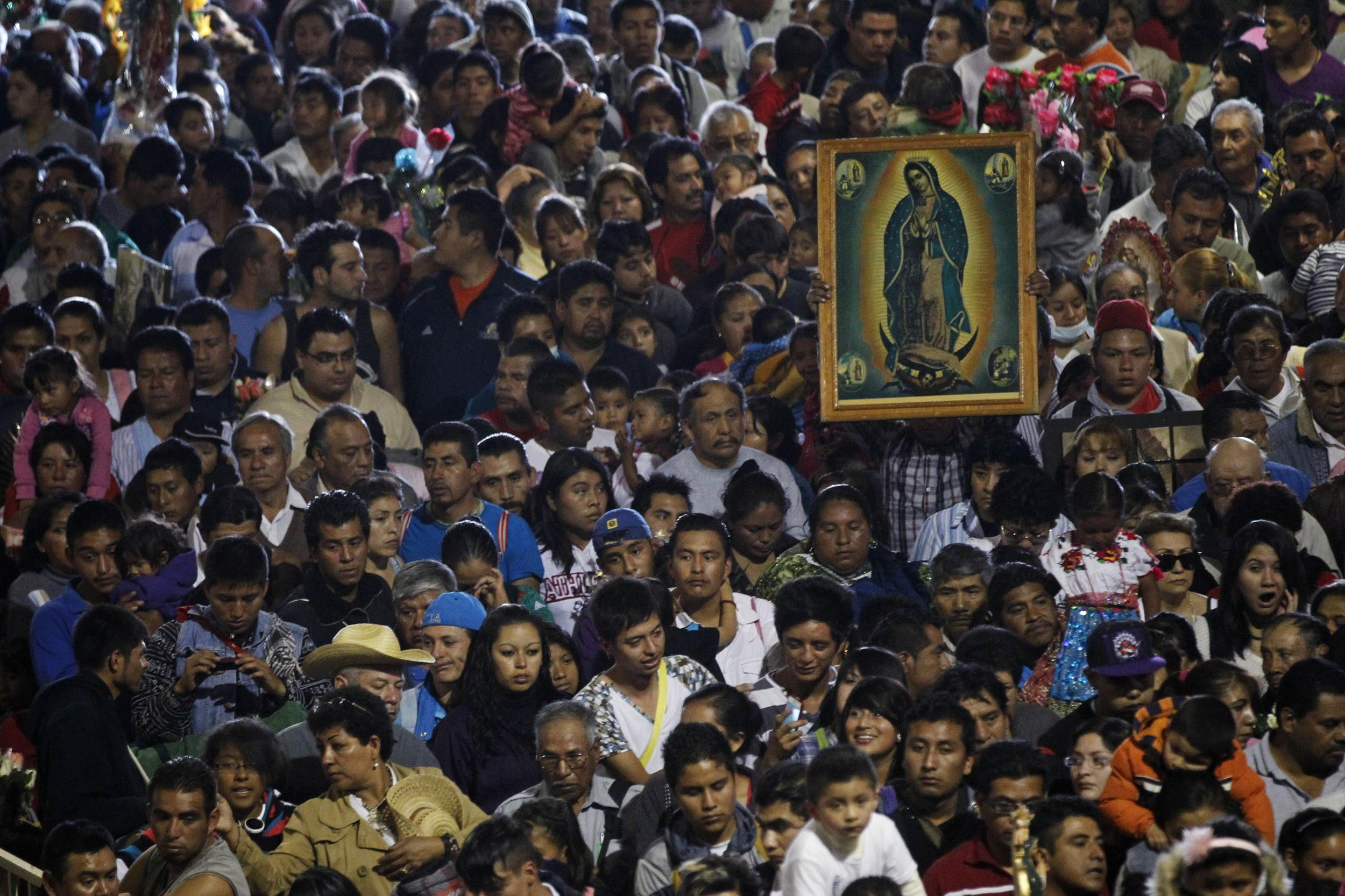 A pilgrim carries a picture of the Virgin of Guadalupe amid the crowd at the Basilica in Mexico City