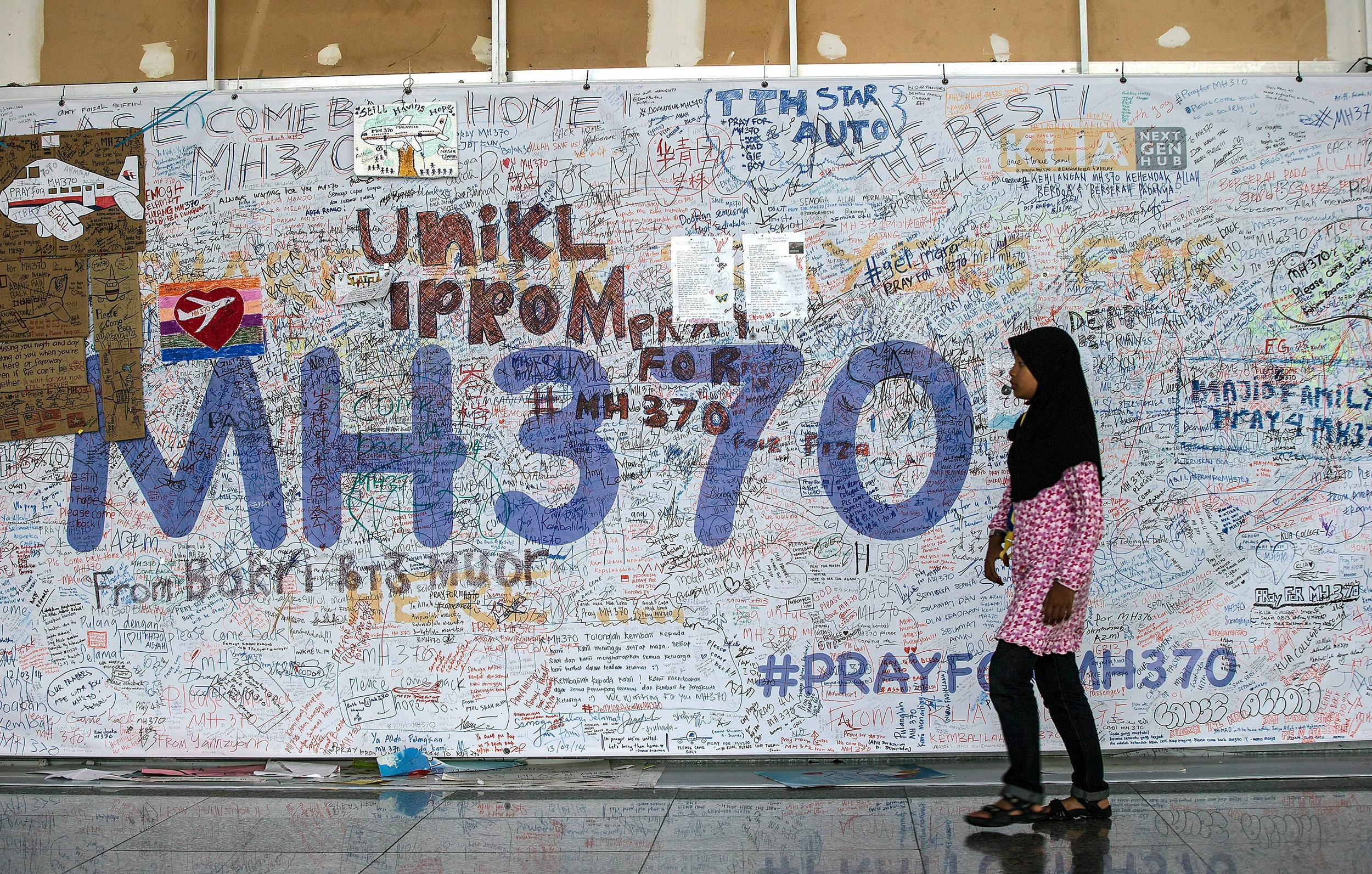 Image: A girl walks in front of the wall of hope for missing Malaysia Airline flight MH370