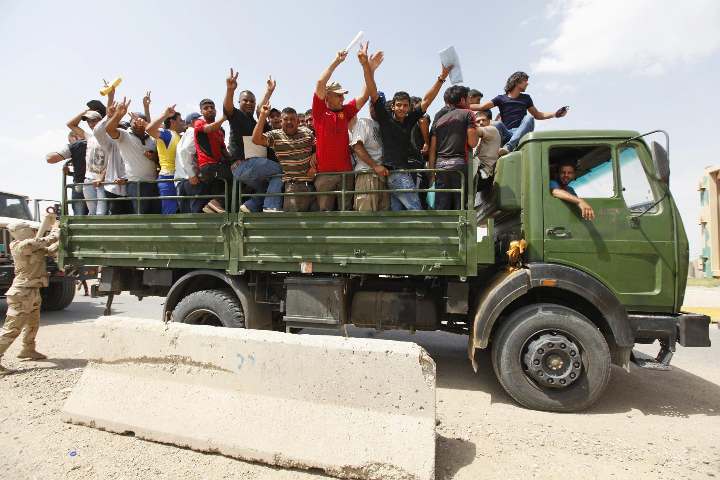 Image: Volunteers who have joined the Iraqi Army to fight against the predominantly Sunni militants who have taken over Mosul and other Northern provinces, gesture from an army truck in Baghdad