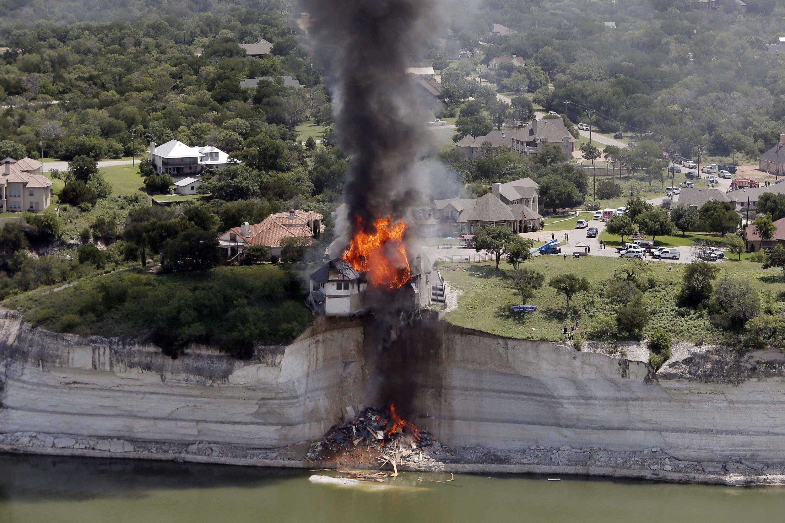 Image: Smoke rises from a house deliberately set on fire, days after part of the ground it was resting on collapsed into Lake Whitney