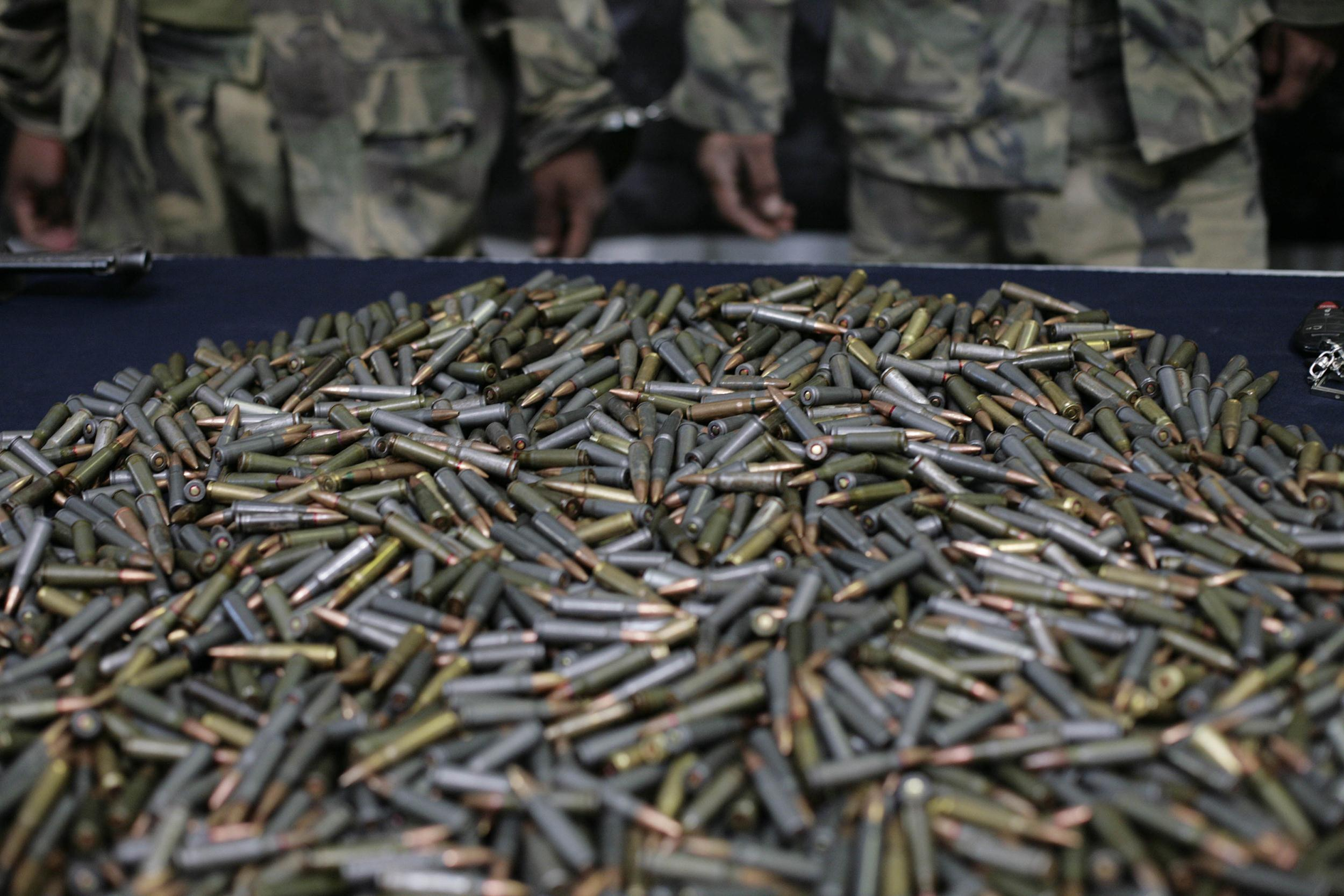 Image: AK-47 ammunition sits on a table  in front of 18 alleged members of the drug cartel El Milenio during a presentation to the press in Guadalajara, Mexico, on May 23, 2010.