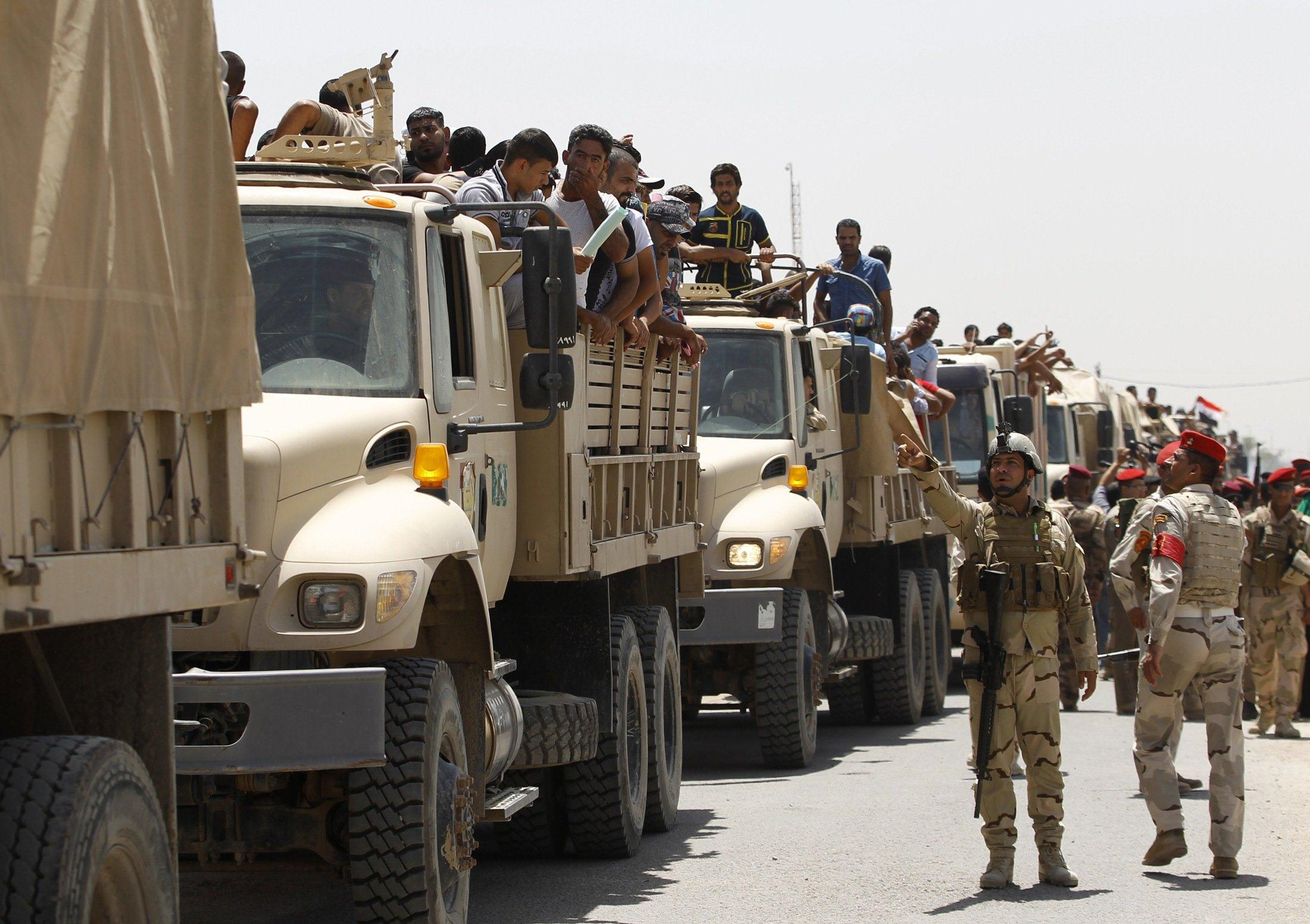 Image: Volunteers who have joined the Iraqi Army to fight against the predominantly Sunni militants travel in army trucks in Baghdad