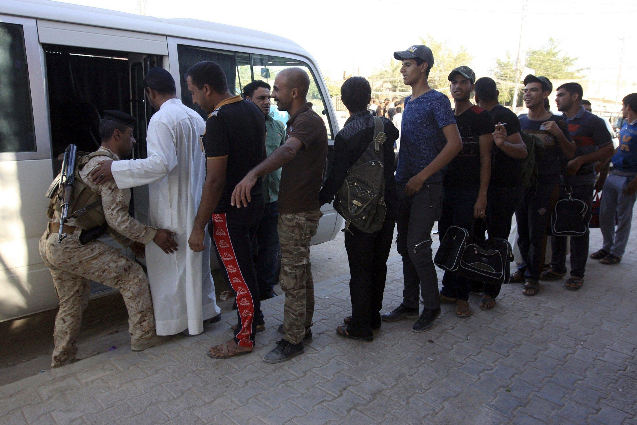 Image: Volunteers, who have joined the Iraqi army to fight against the predominantly Sunni militants from the radical Islamic State of Iraq and the Levant (ISIL) who have taken over Mosul and other northern provinces, prepare to board a bus in Kerbala