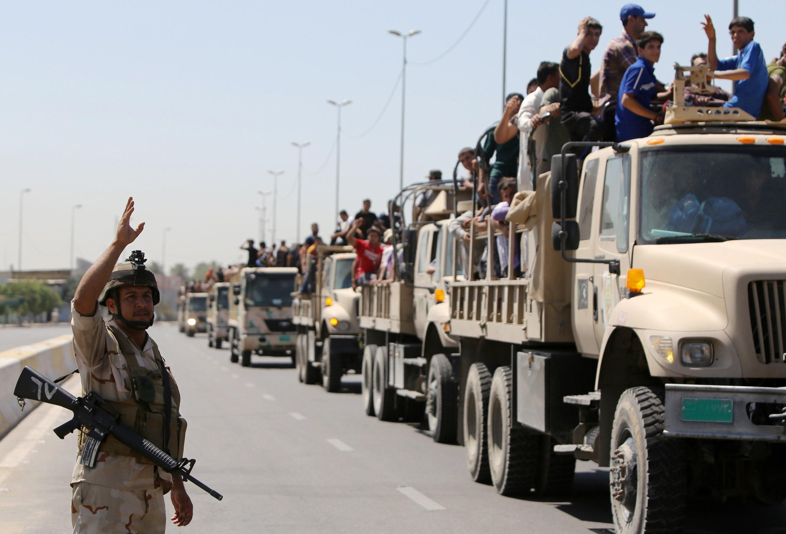 Image: An Iraqi soldier waves as trucks carrying volunteers to fight along side the Iraqi security forces against Jihadist militants leave a recruitment center in Baghdad