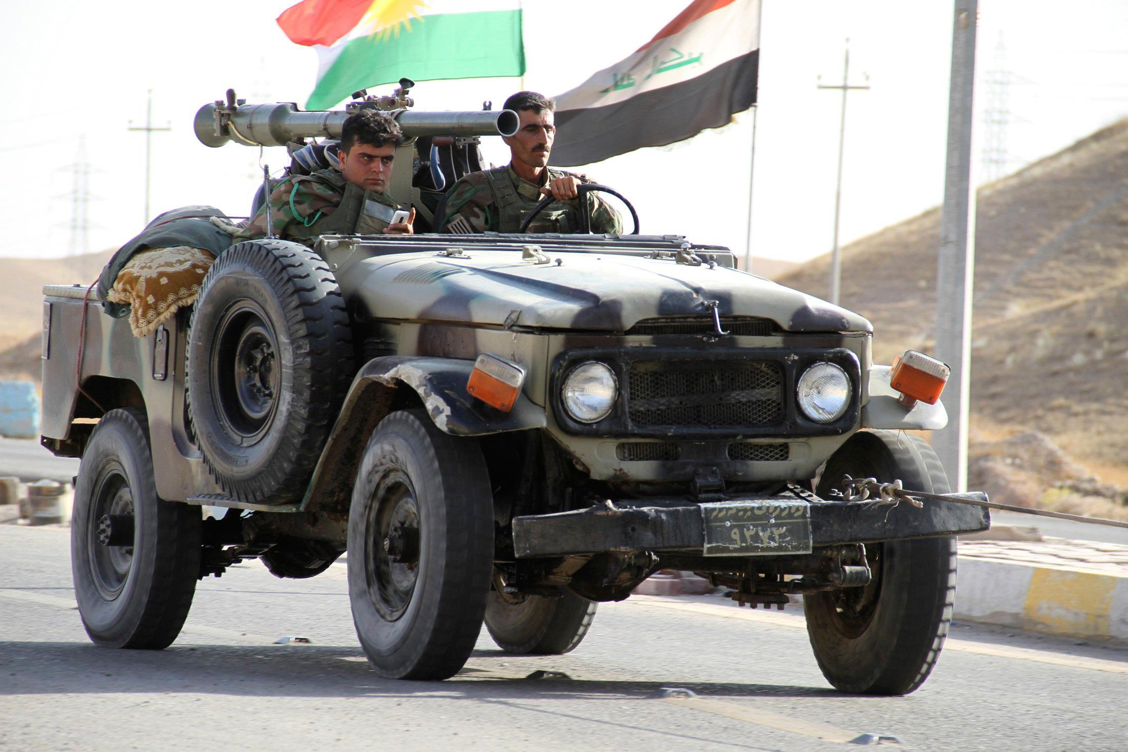 Image: Members of Kurdish security forces travel in a vehicle during clashes with ISIL on the outskirts of Diyala