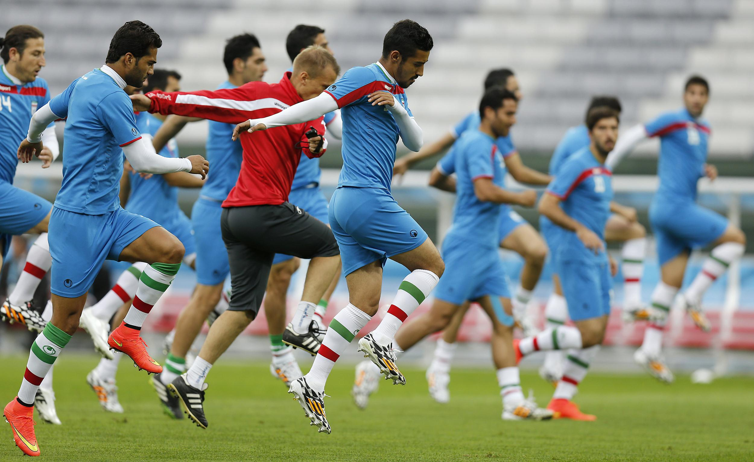 Image: Iran players stretch to warm up during an official training session